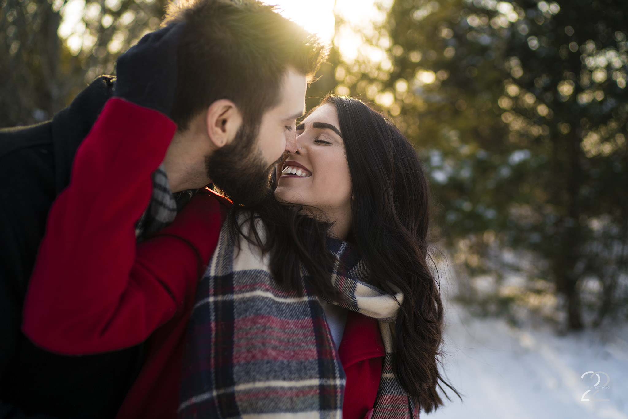 Woman pulls a man in for a kiss, both smiling, in the snow at sunset at Oakes Quarry Park by Dayton Wedding Photographer Studio 22 Photography
