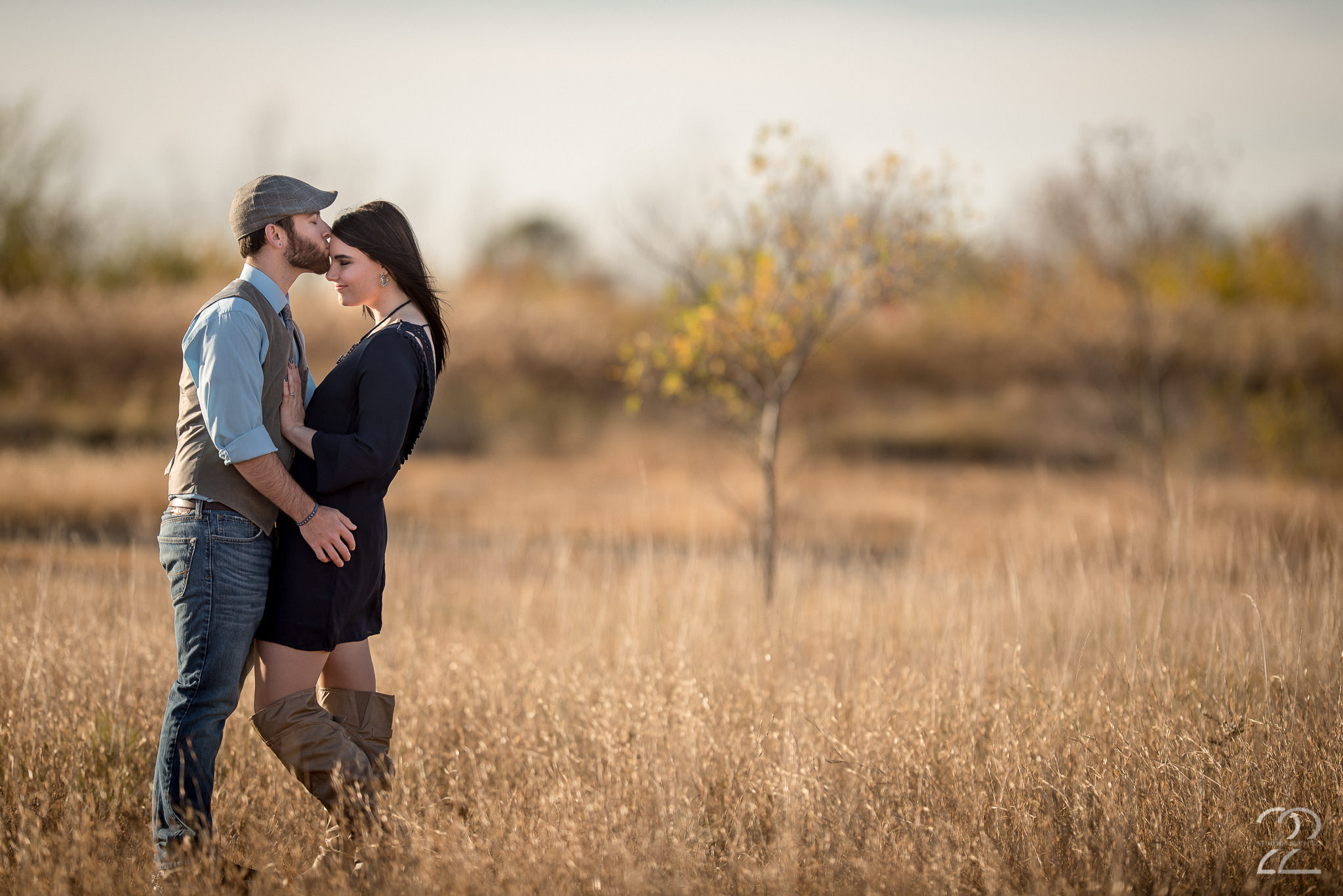 Man in jeans and vest kisses woman in dress in tall grass at Oakes Quarry Park by Dayton Wedding Photographer Studio 22 Photography