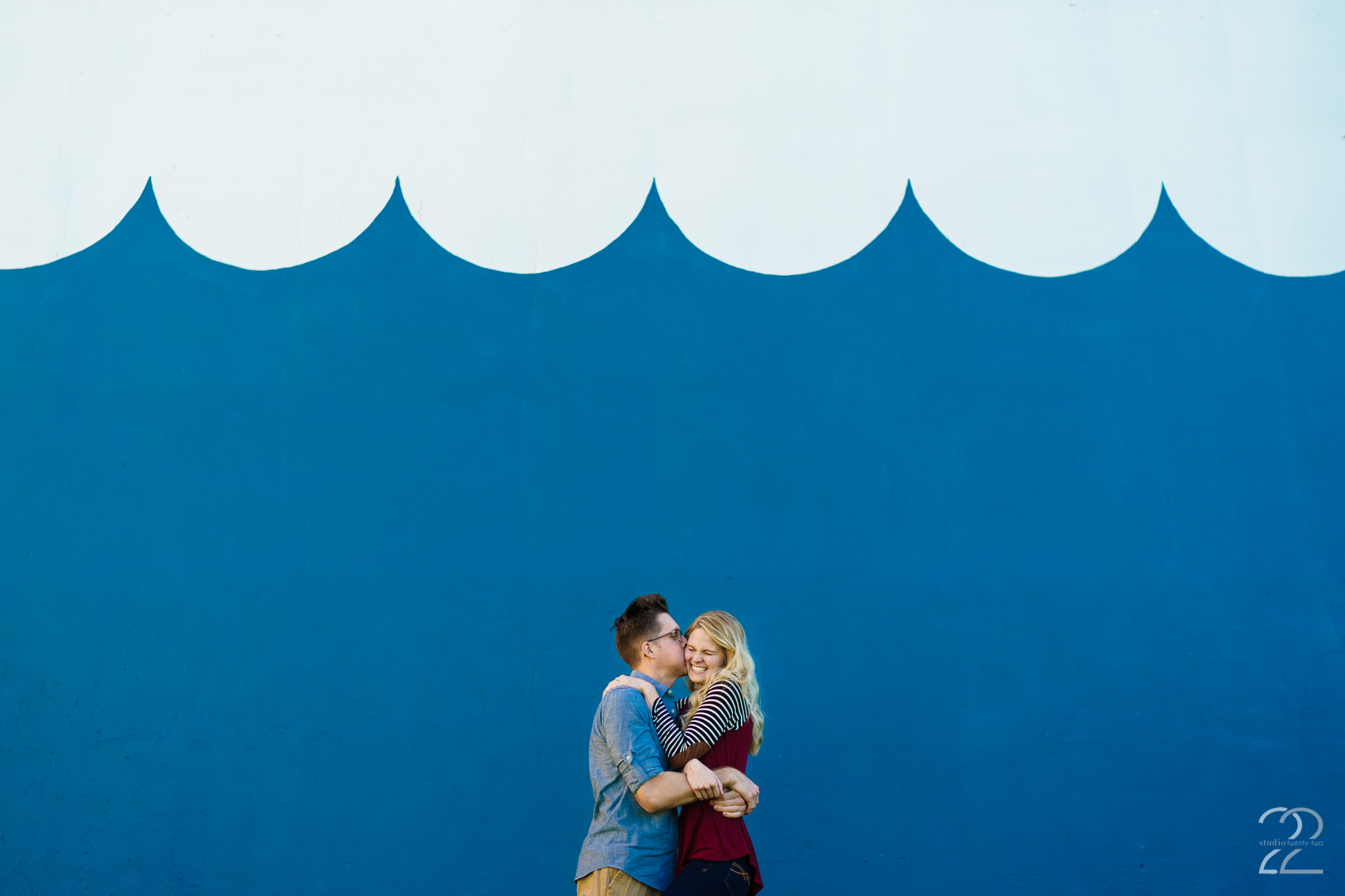 A man gives a big kiss on a woman's cheek near Riverscape Metropark by Dayton Wedding Photographer Studio 22 Photography