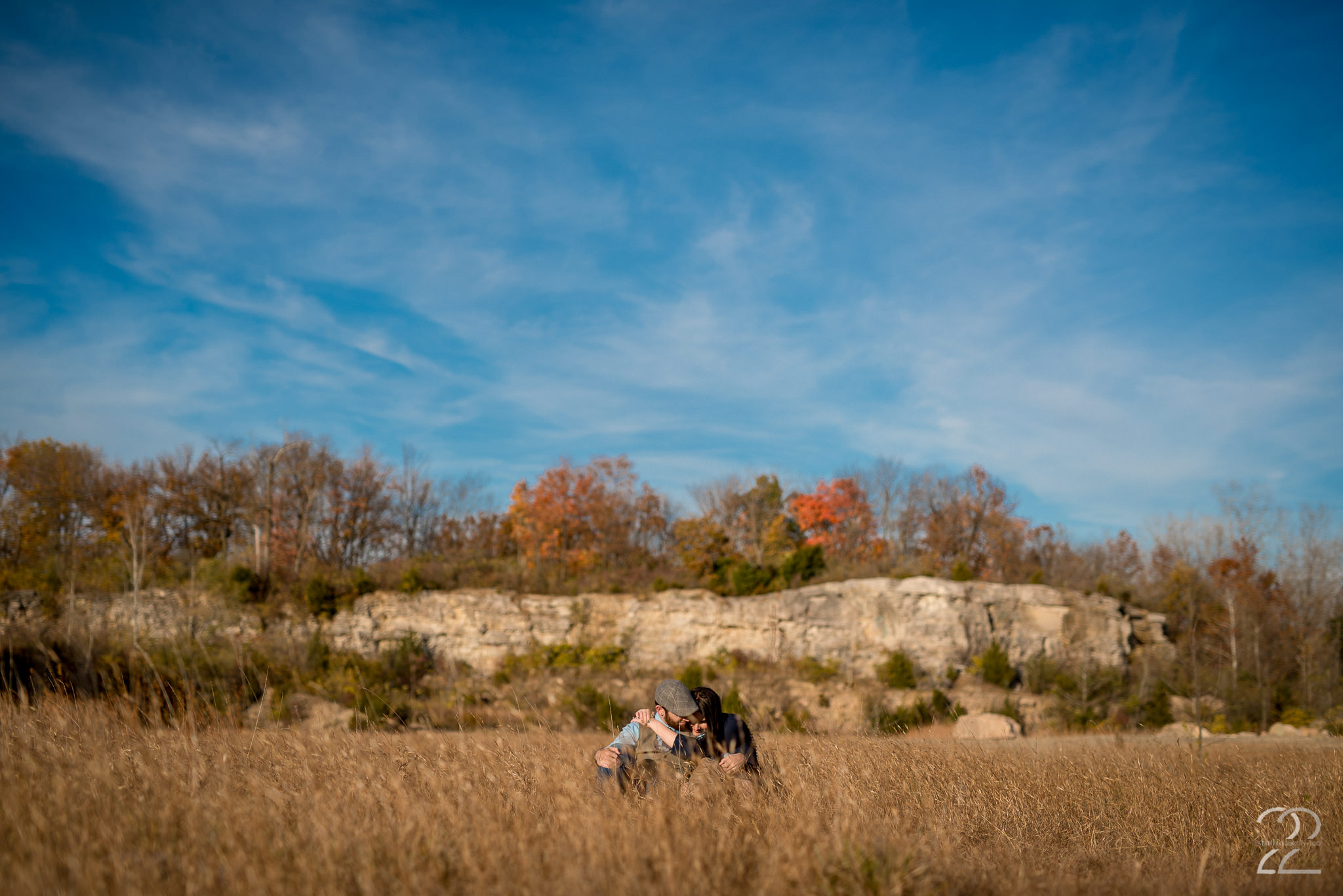 Man and woman embrace in tall grass in autumn, with a cliff and blue sky behind them at Oakes Quarry Park by Dayton Wedding Photographer Studio 22 Photography