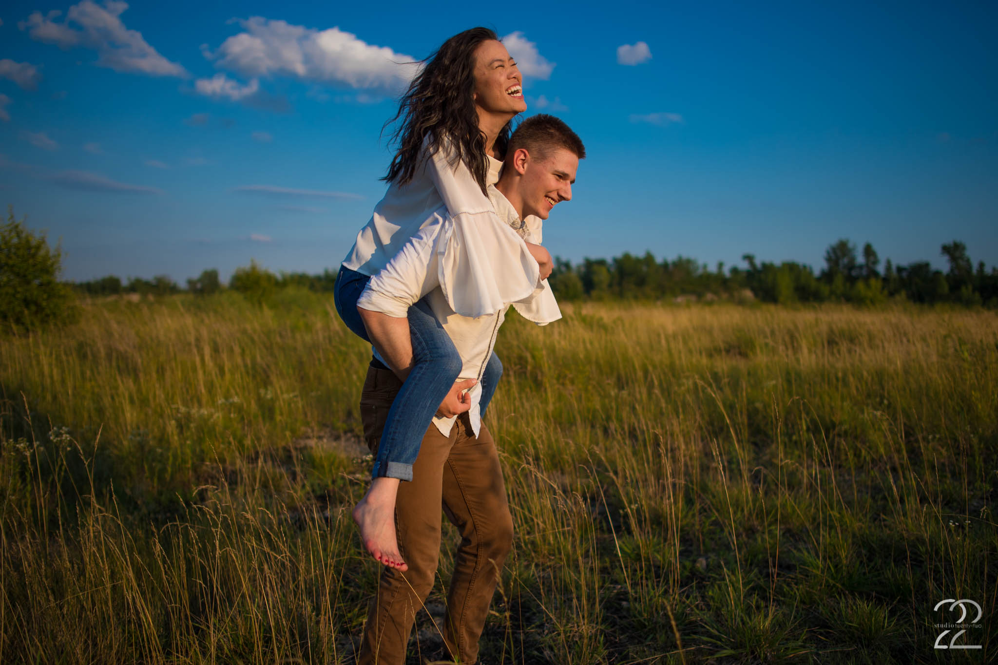 Woman rides piggy back on a man's back, laughing as they run through a field with a blue sky behind them at Oakes Quarry Park by Dayton Wedding Photographer Studio 22 Photography
