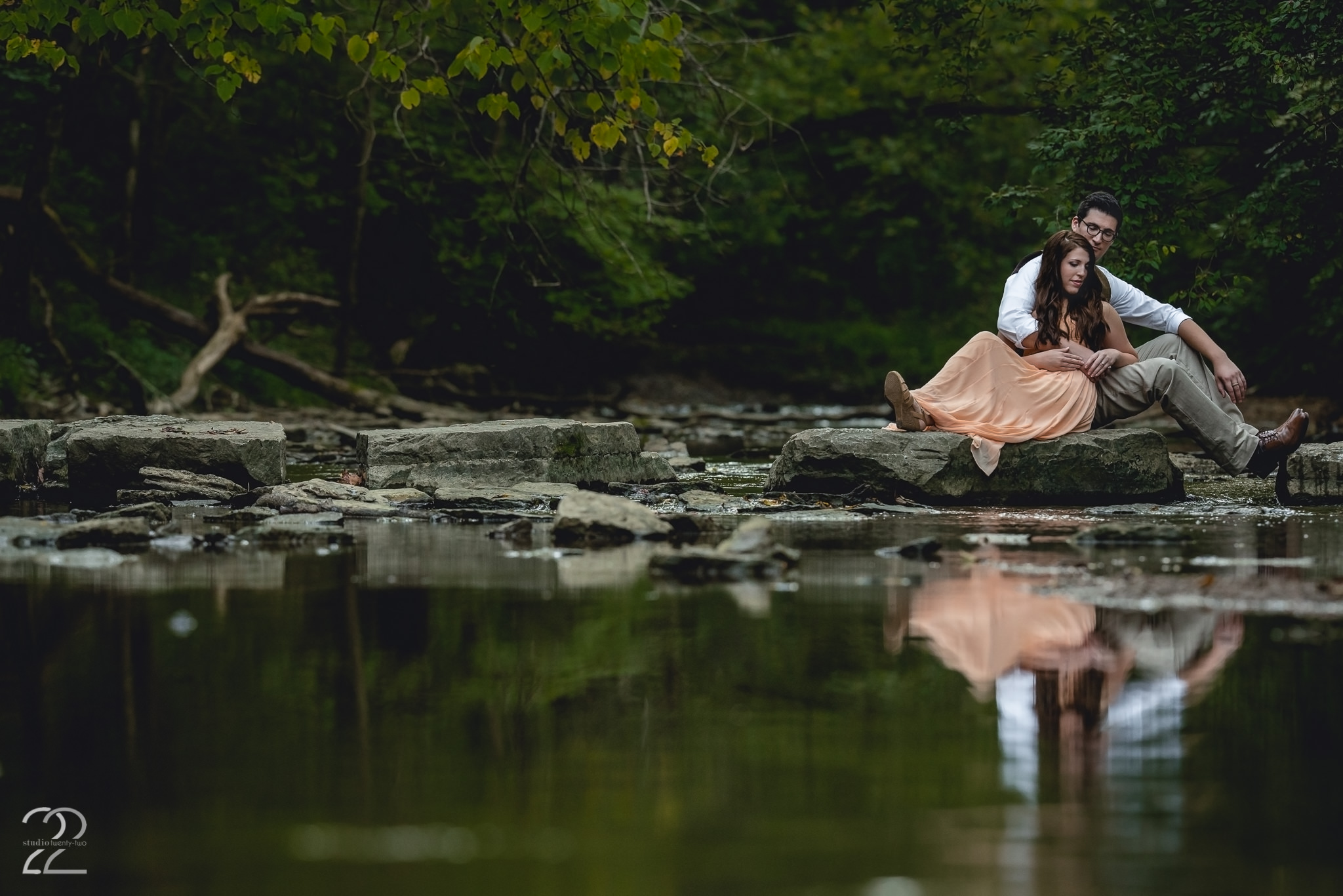 Man and woman sit together on a path of rocks along a creek at Sugarcreek Metropark by Dayton Wedding Photographer Studio 22 Photography