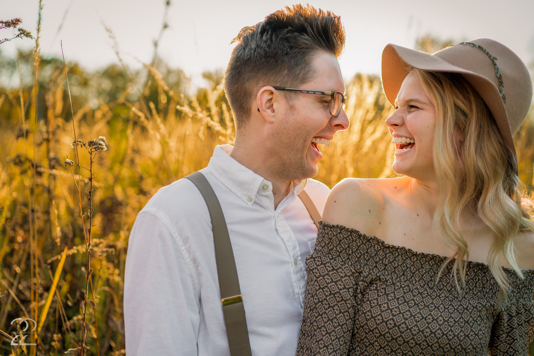 Man and woman laugh together in a field during sunset at Wegerzyn Garden Metropark by Dayton Wedding Photographer Studio 22 Photography