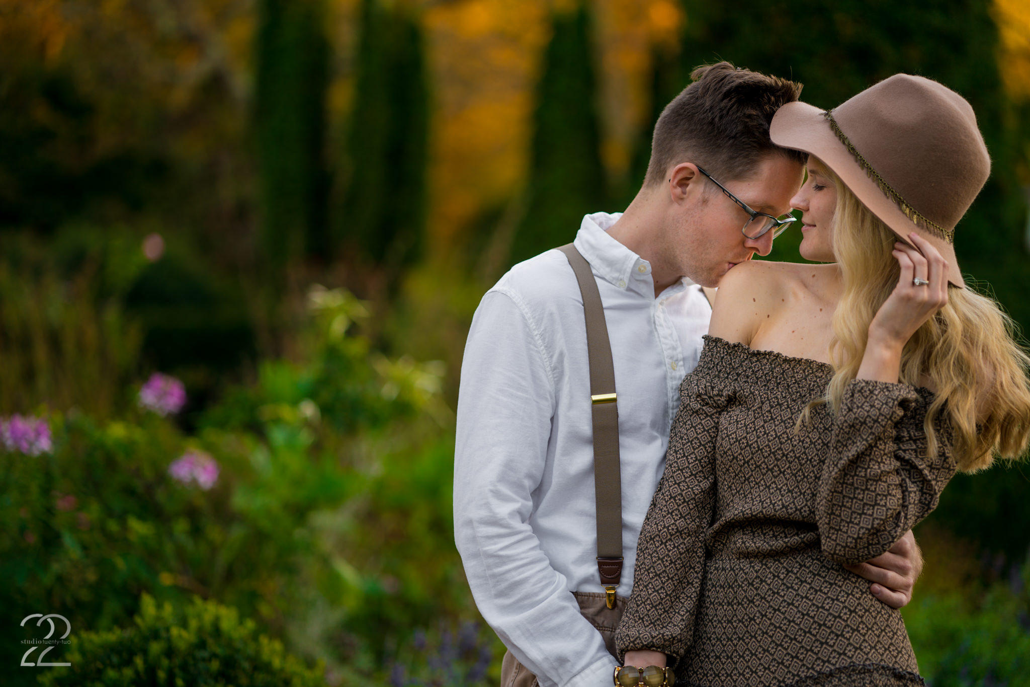 Man kisses woman's shoulder as he hugs her in a garden at Wegerzyn Garden Metropark by Dayton Wedding Photographer Studio 22 Photography