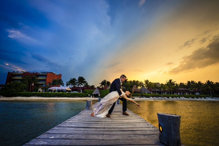 Groom dipping bride on dock at sunset
