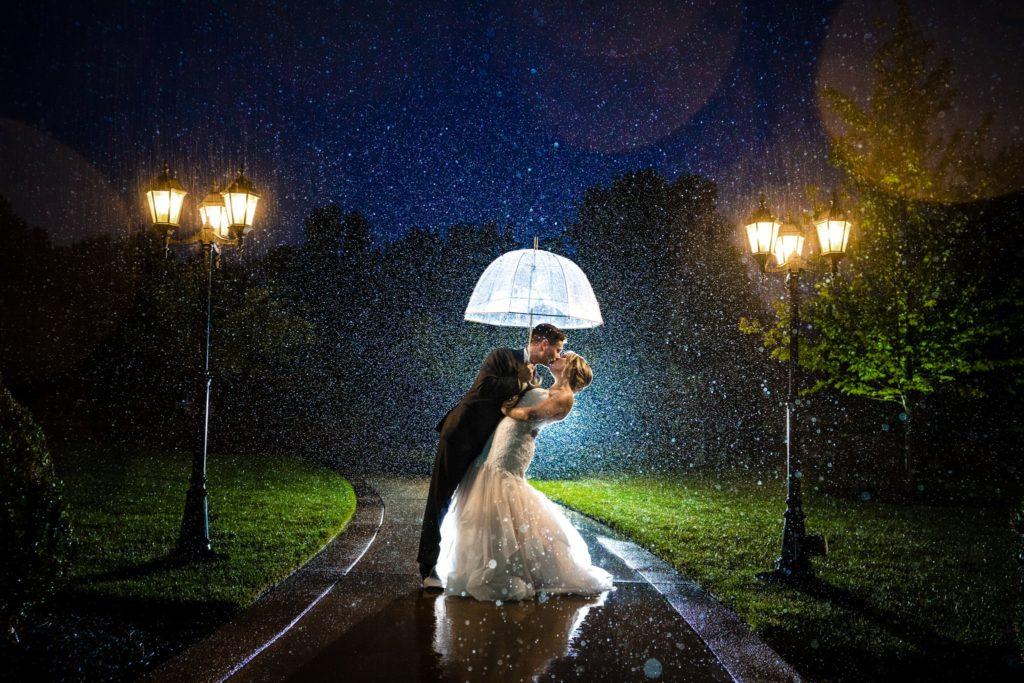 Husband and wife kiss in the rain underneath an umbrella at night at Cincinnati Wedding Venue the Manor House by Cincinnati Wedding Photographer Studio 22 Photography