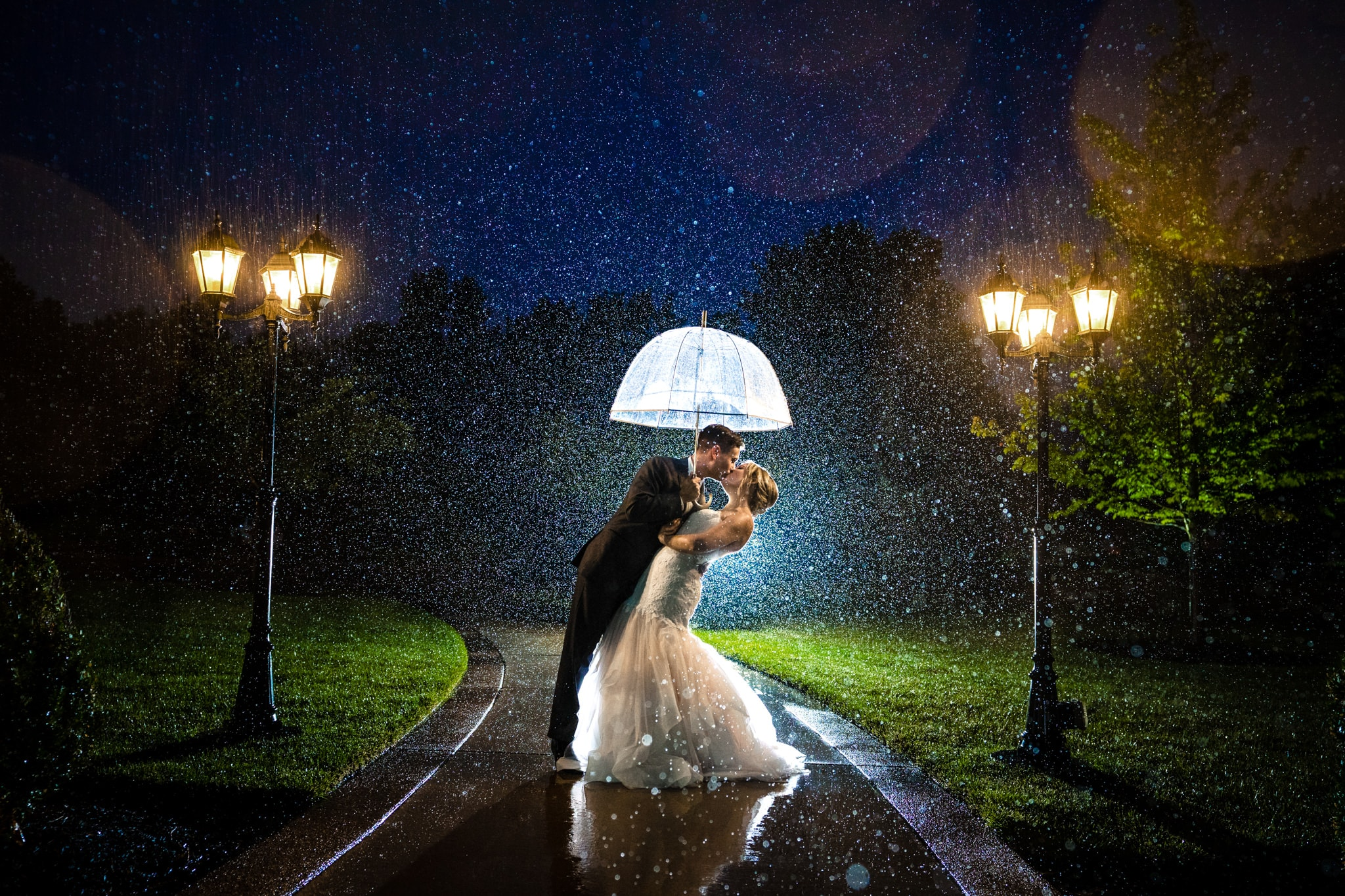 Husband and wife kiss in the rain underneath an umbrella at night at Cincinnati Wedding Venue the Manor House by Cincinnati Wedding Photographer Studio 22 Photography