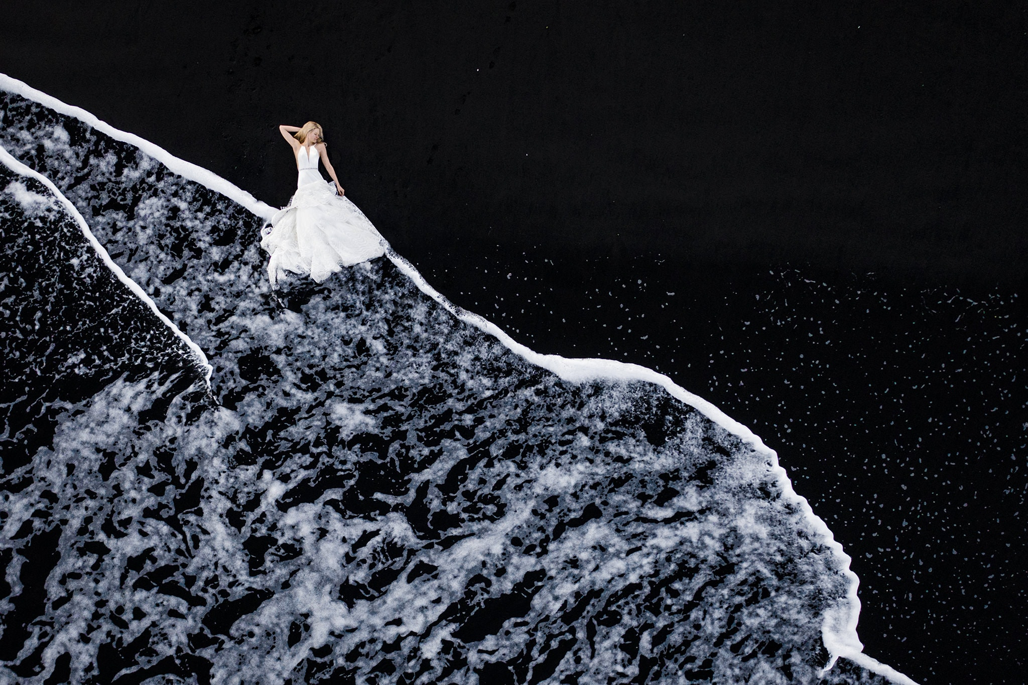 Bride lying on black sand beach