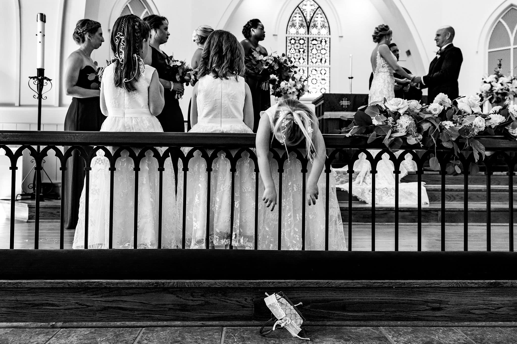 Flower Girl leaning over railing for flower basket