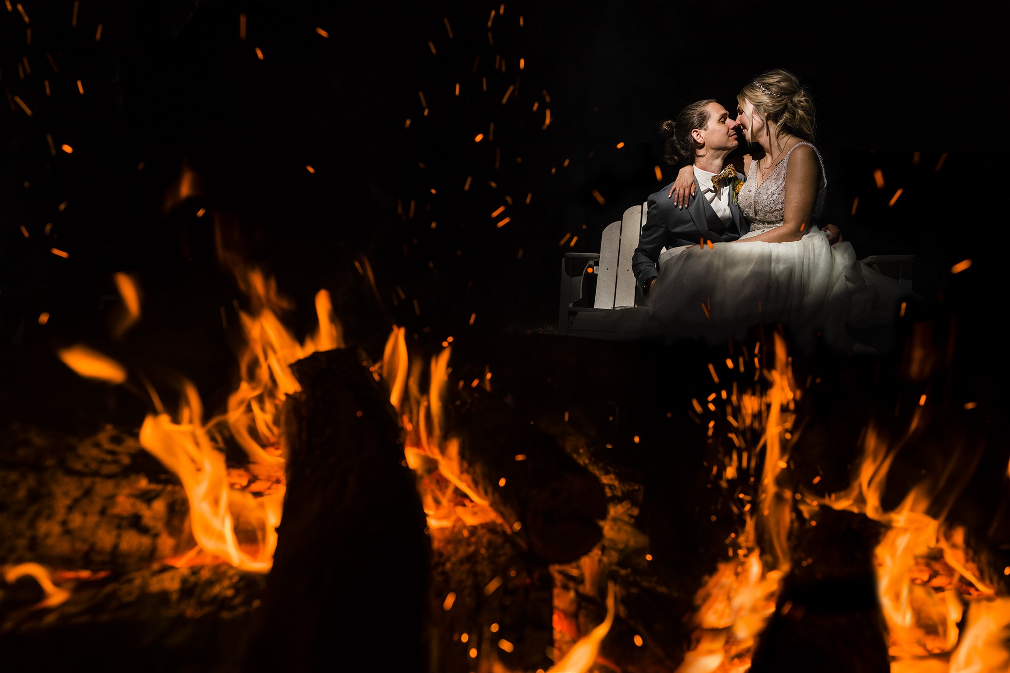 Bride and groom snuggling by bonfire