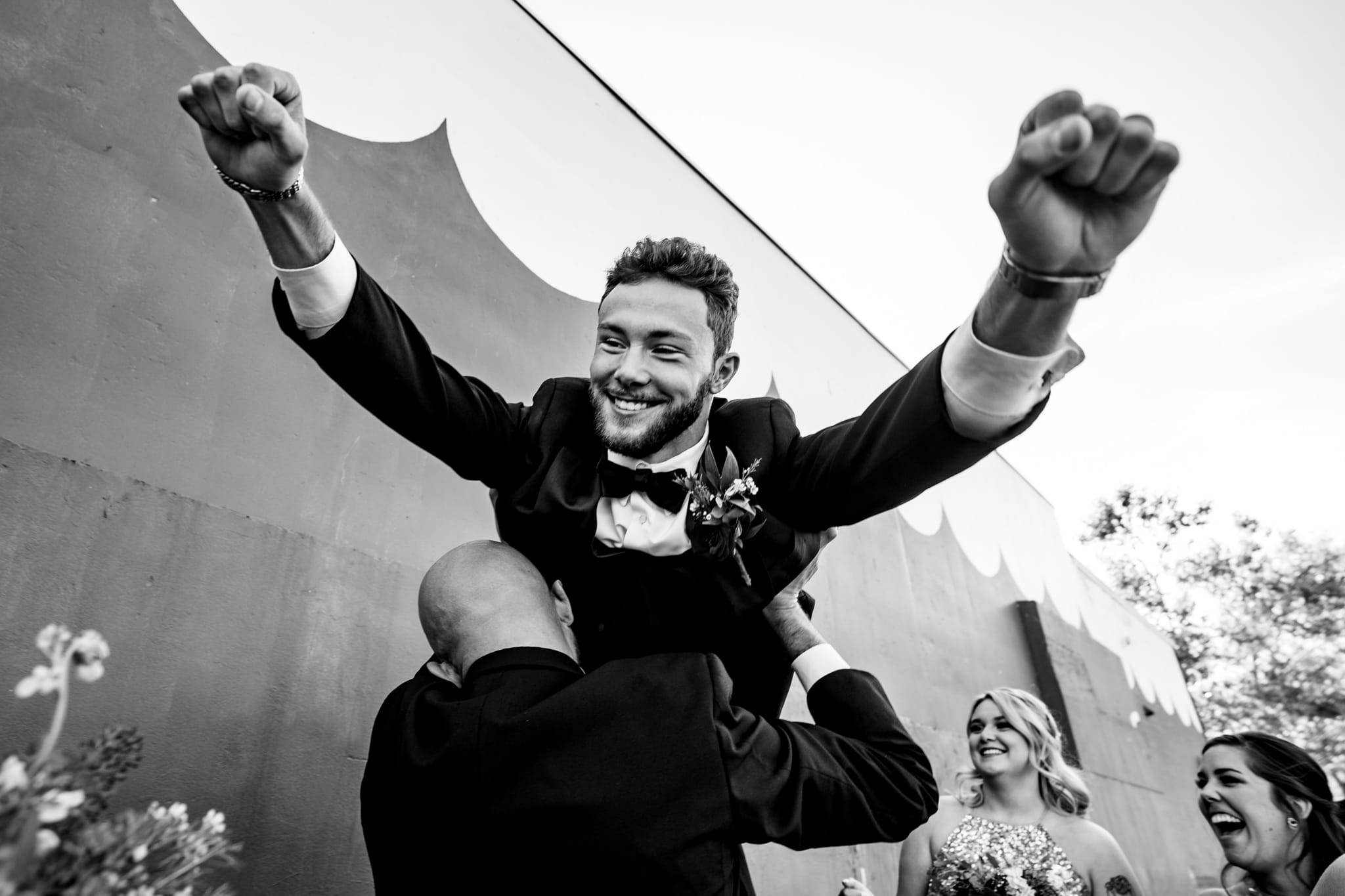 Groom lifted up with hands in air