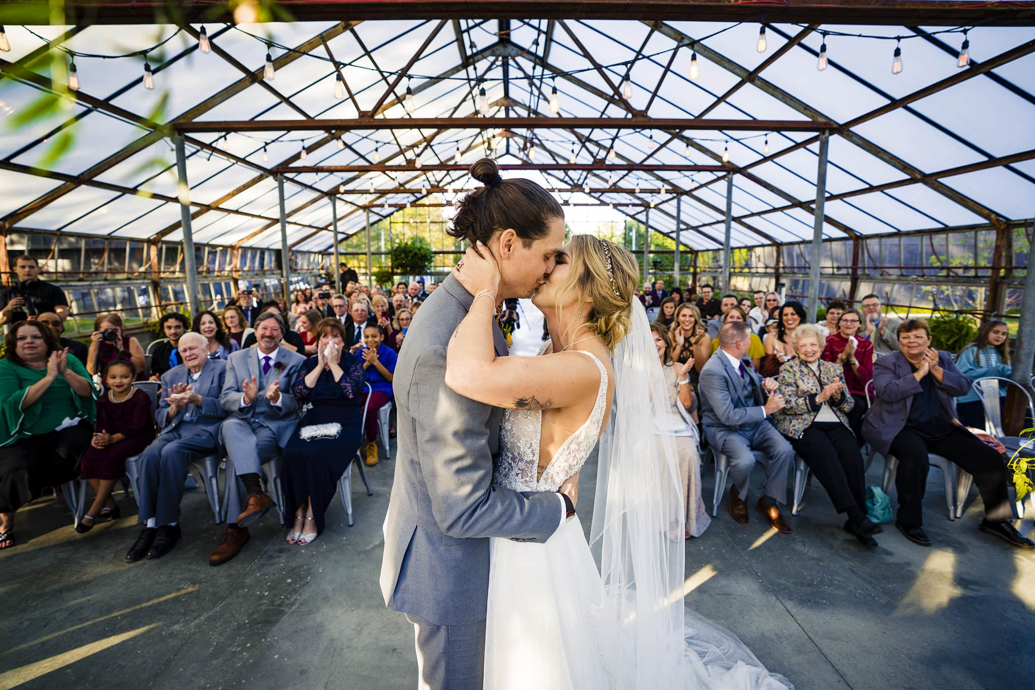 Bride and groom kiss in modern greenhouse wedding