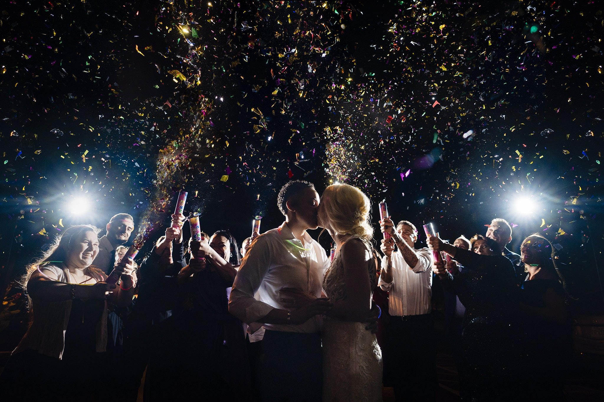 women kissing at wedding with confetti