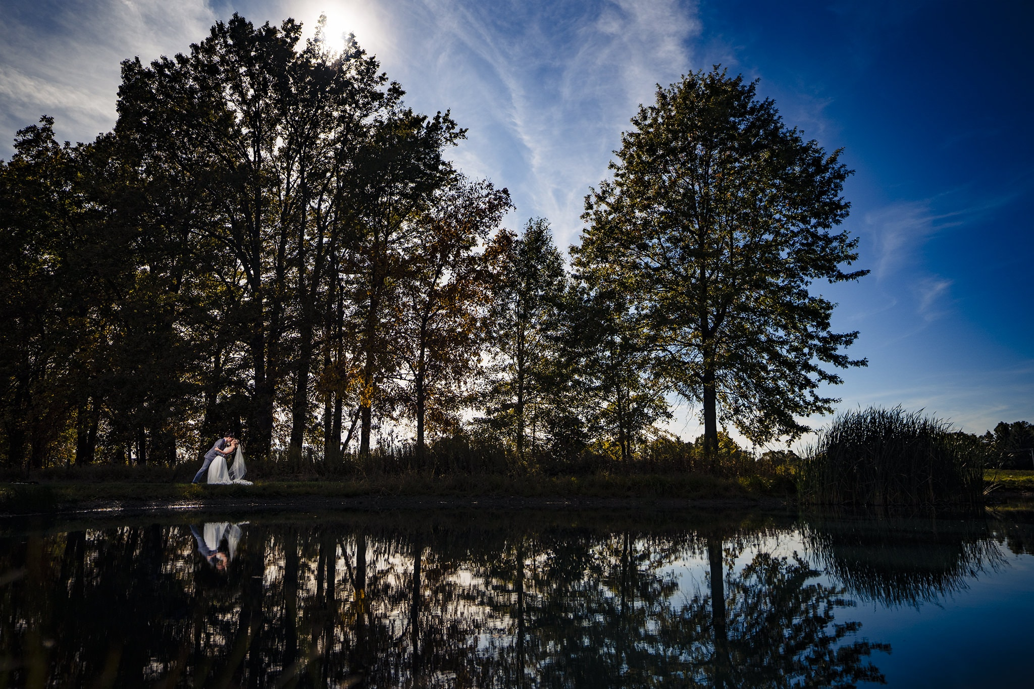 Romantic photo of bride and groom with reflection in lake