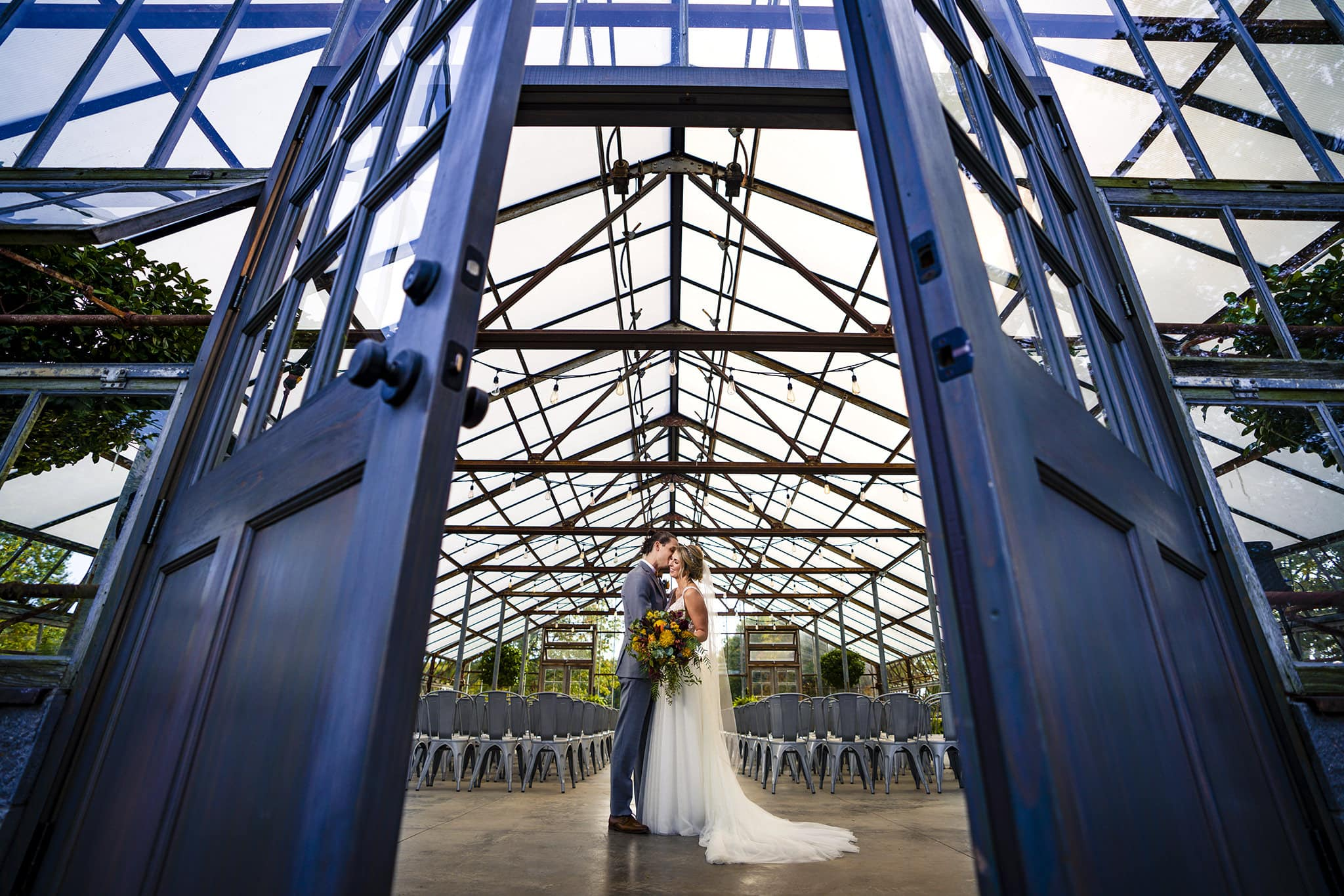 Bride and Groom kissing in greenhouse