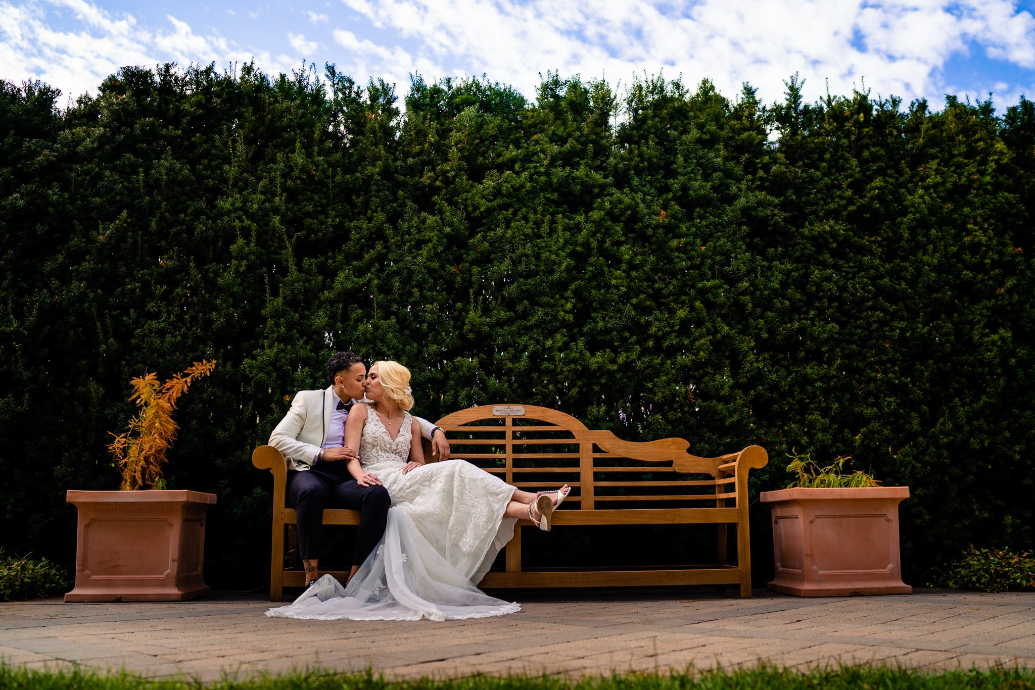Two brides sit on a park bench in autumn