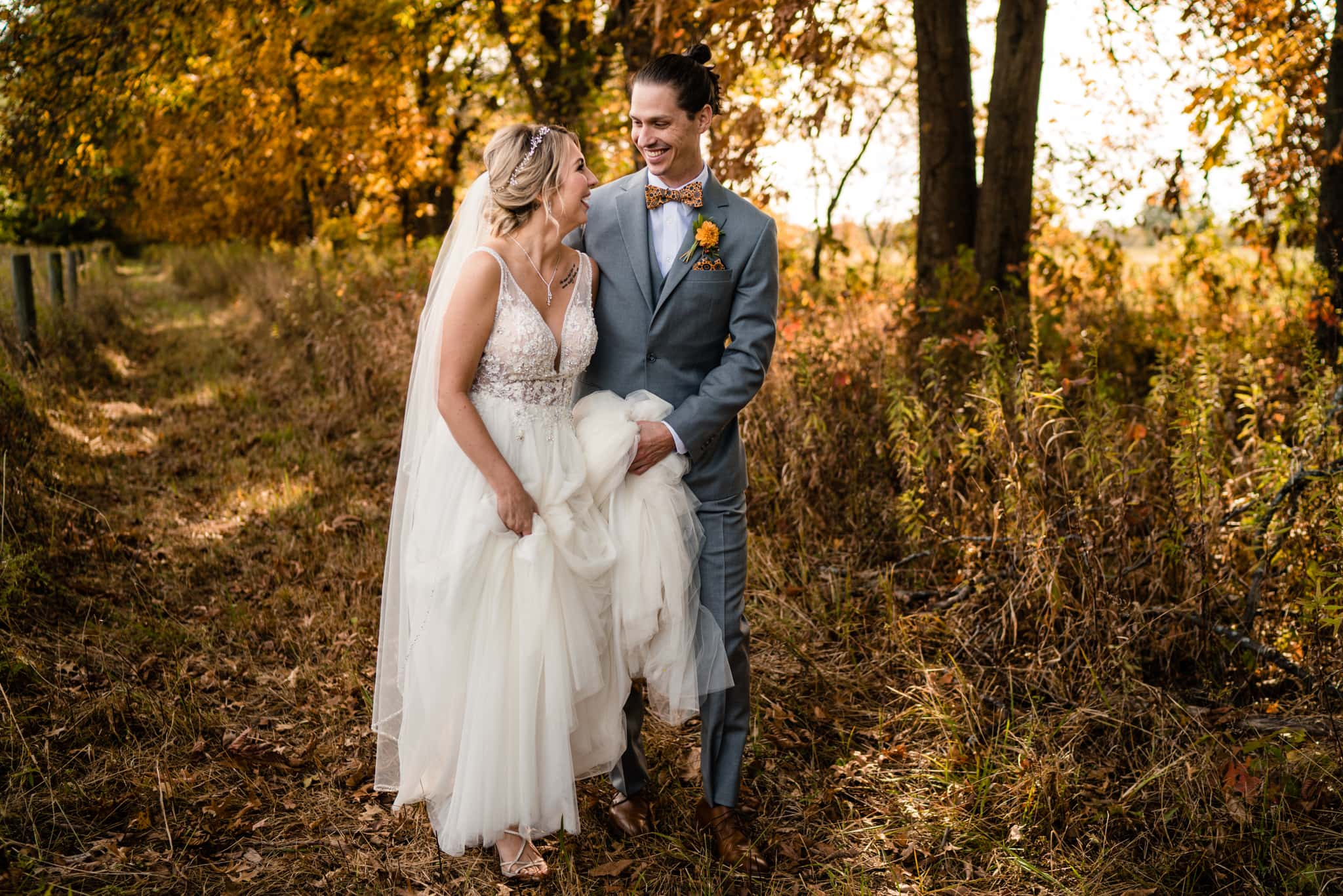 Bride and groom walking down path at modern greenhouse wedding