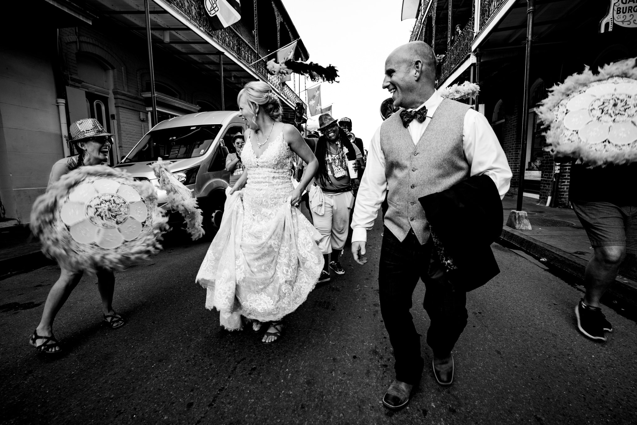 Bride and groom laughing in parade in New Orleans