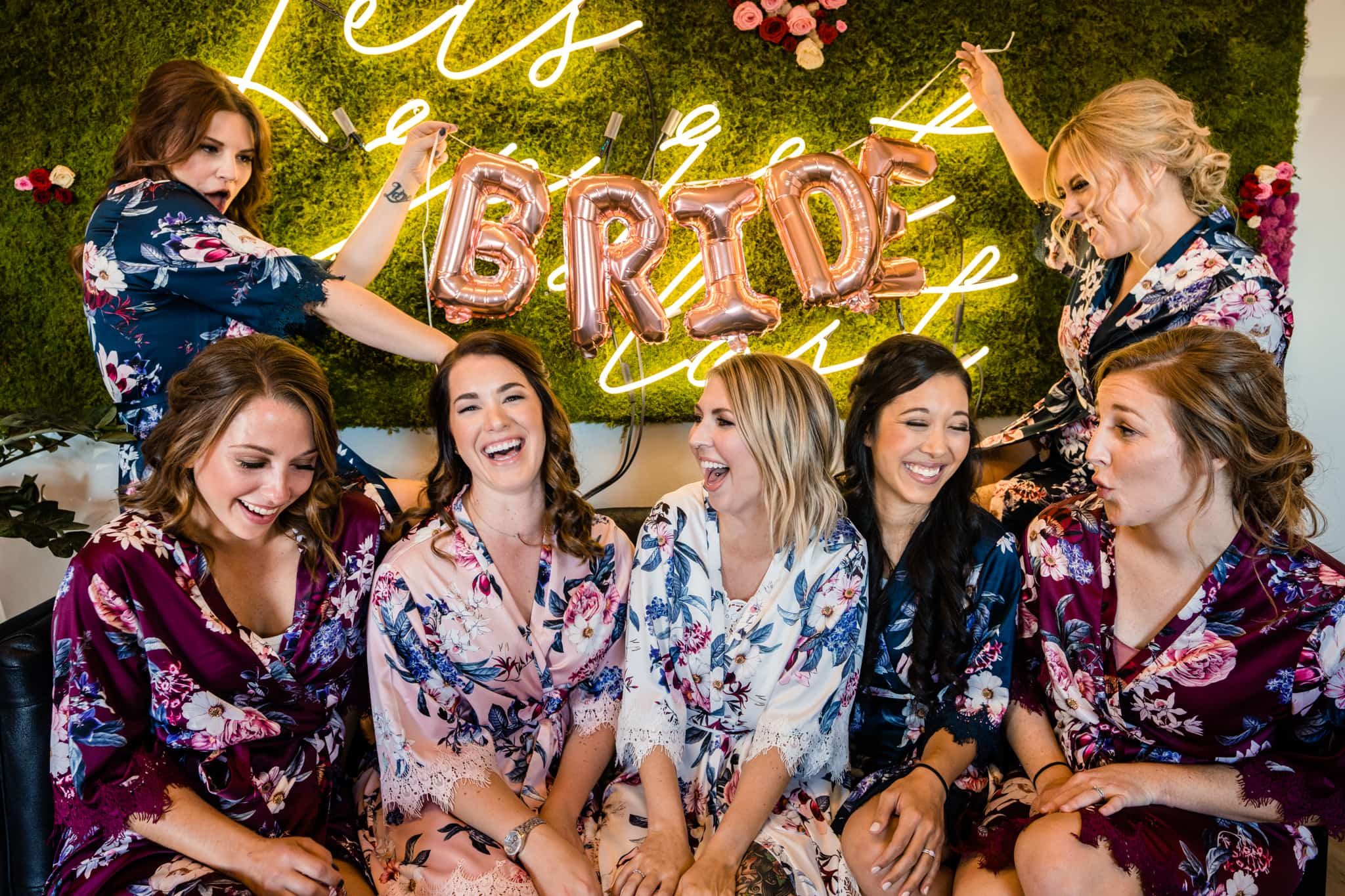 Bride and bridesmaids laugh together before modern greenhouse wedding