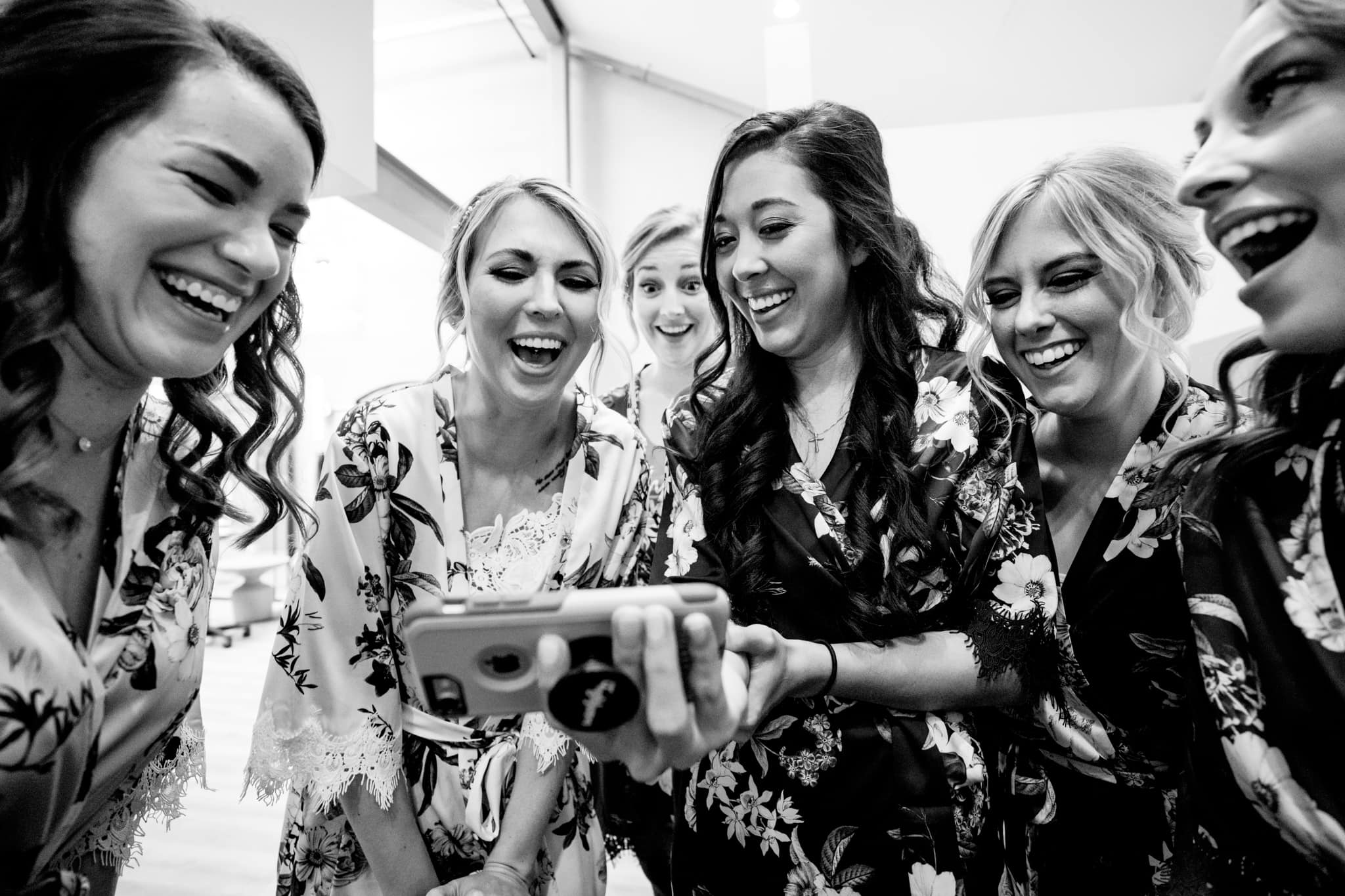 Bride and friends laughing at video