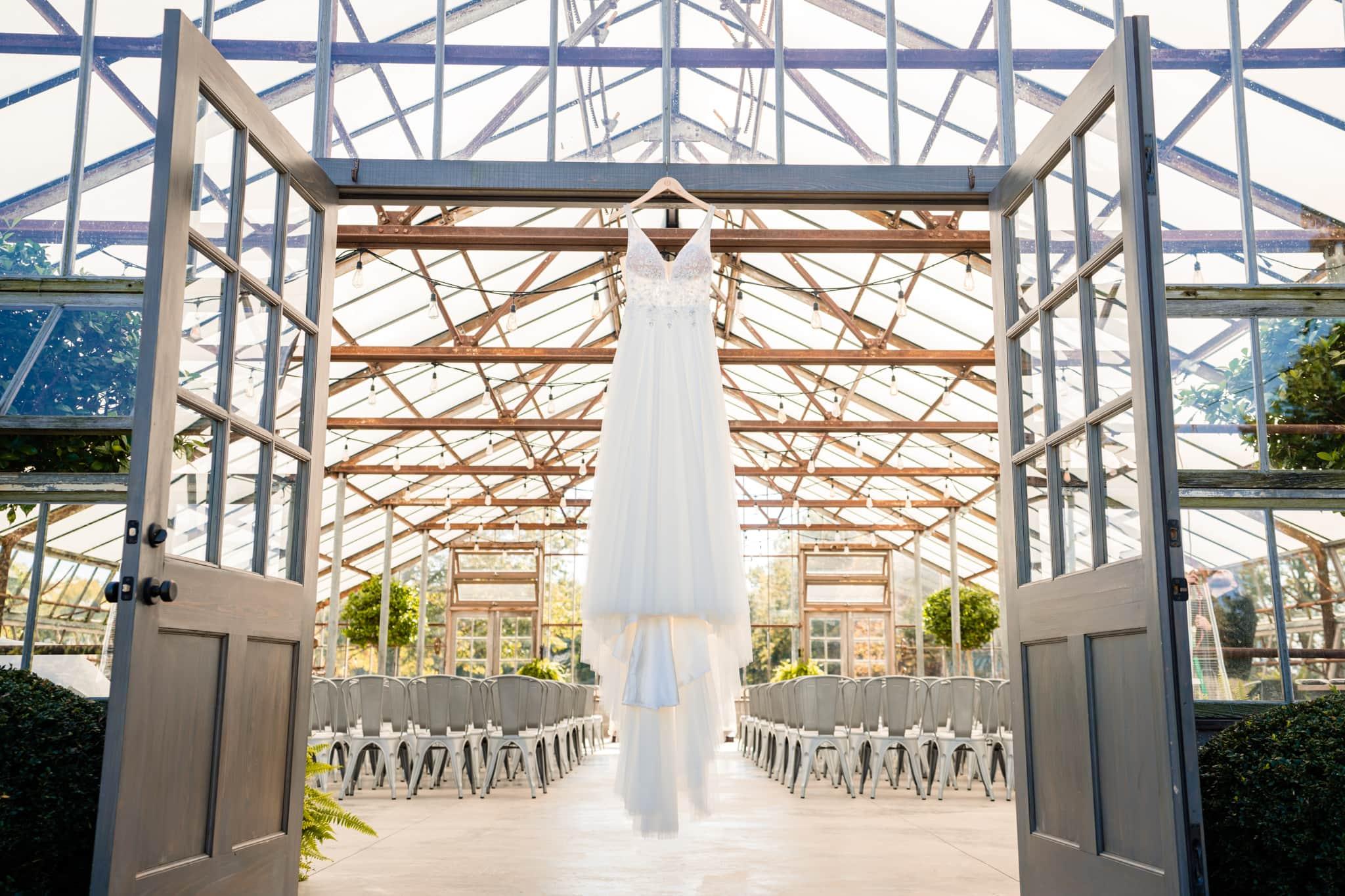 Wedding dress hanging in doorway at modern greenhouse wedding