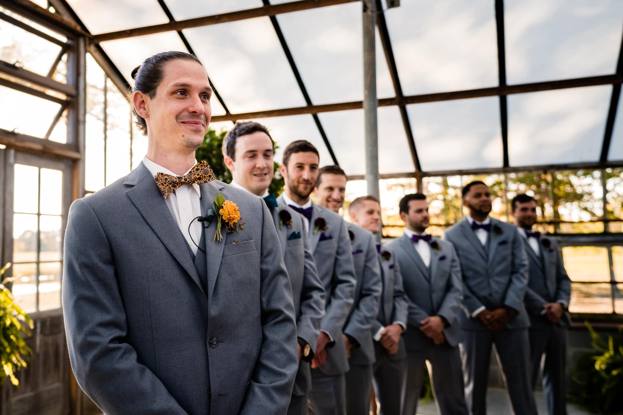 Groom watches bride walk down the aisle at modern greenhouse wedding