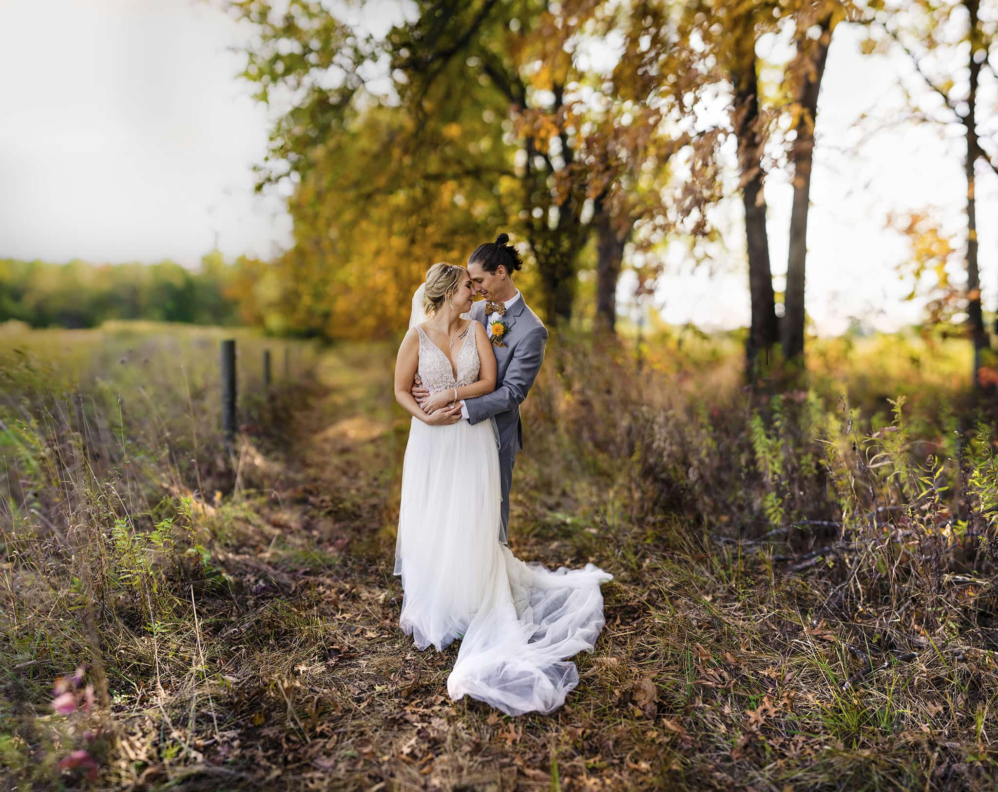 Bride and groom embrace outdoors during fall wedding