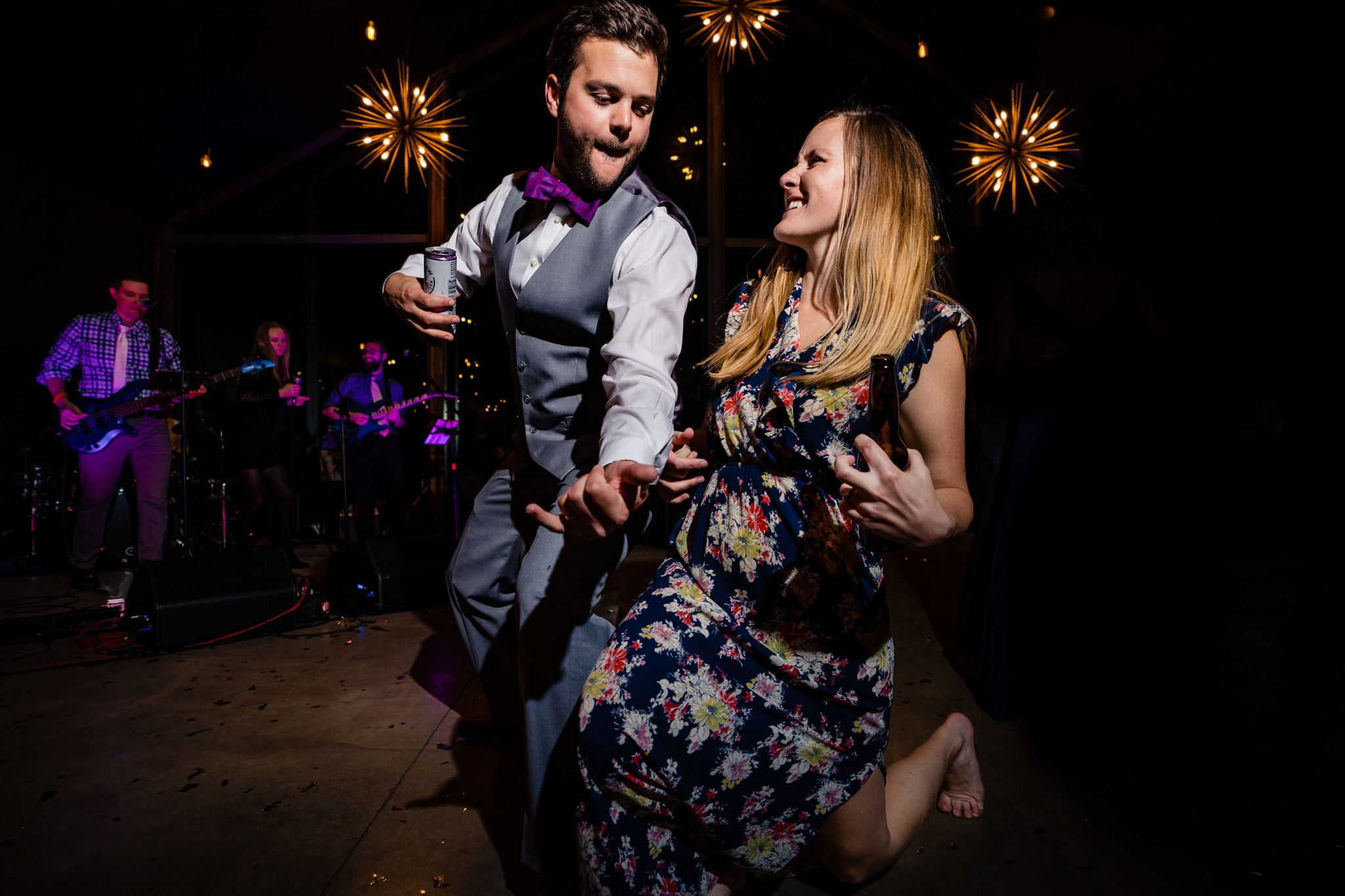 Two wedding guests playing air guitar on dance floor