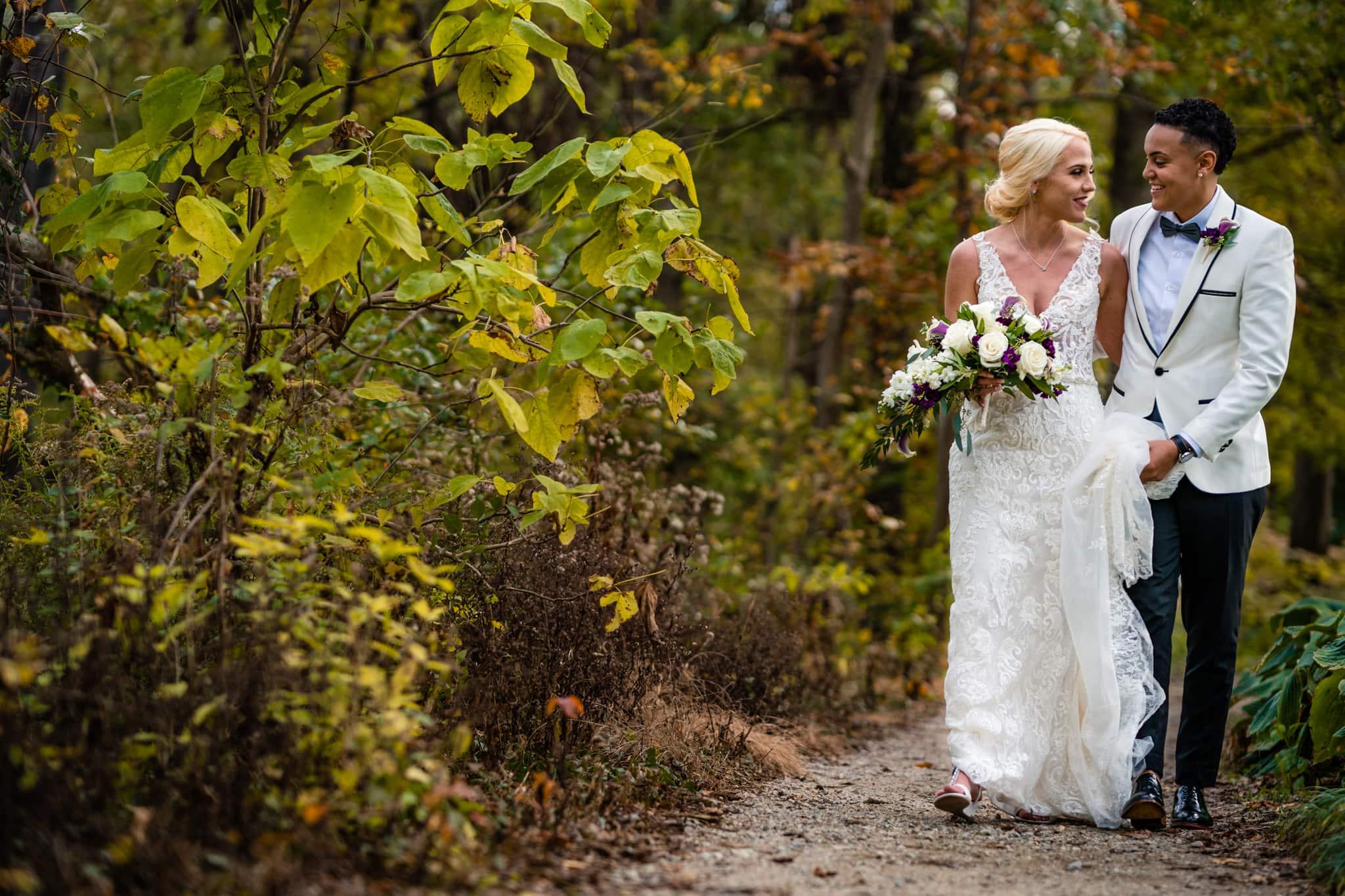 Two brides walk along autumn garden path on wedding day