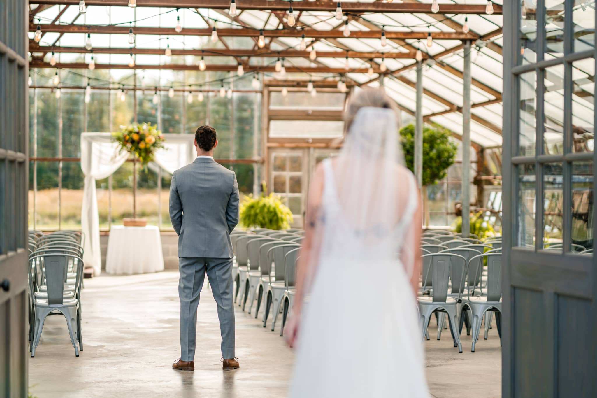 Bride walking to see groom for the first time at modern greenhouse wedding