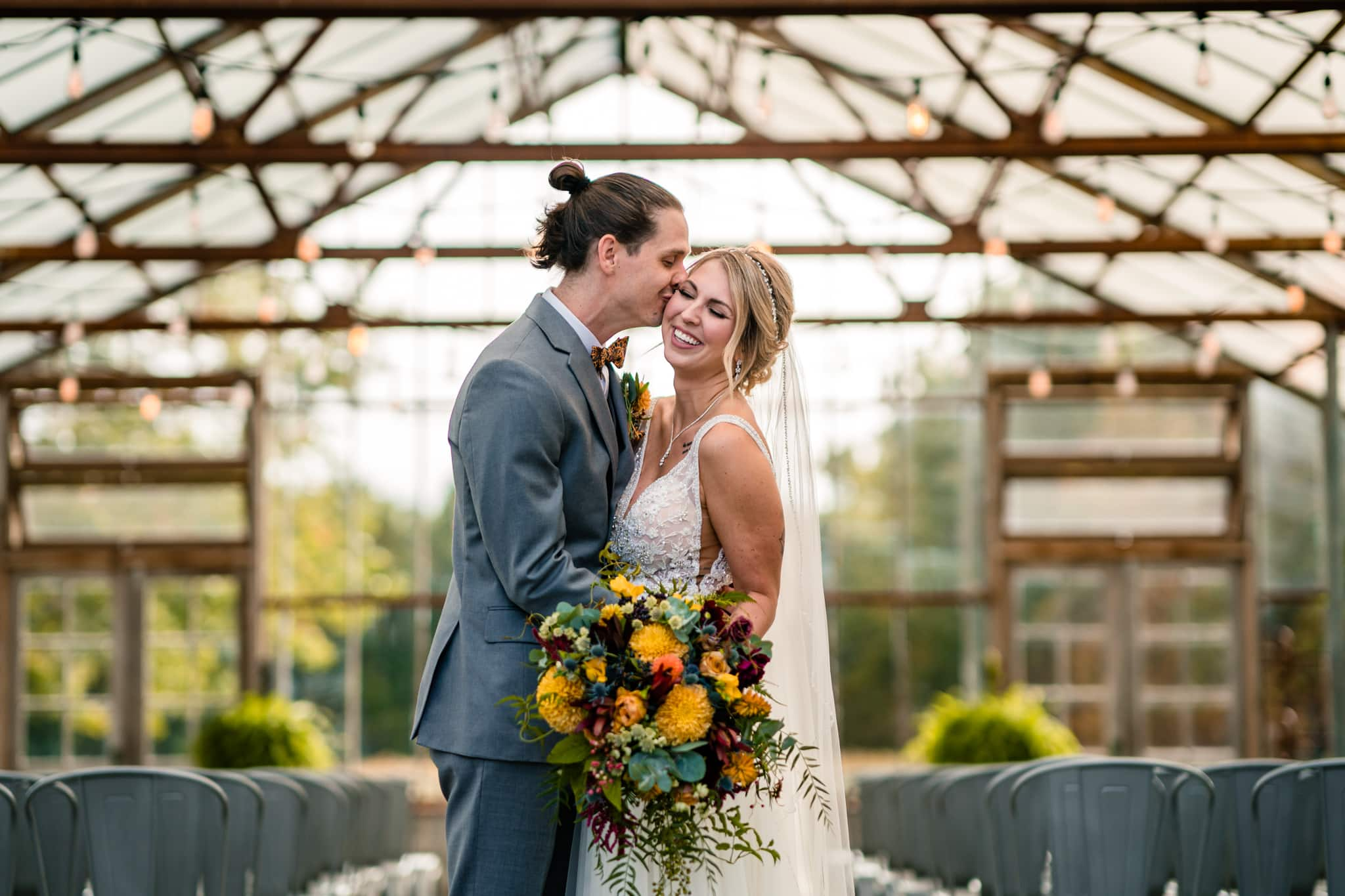 Bride and groom kissing at a Modern Greenhouse Wedding