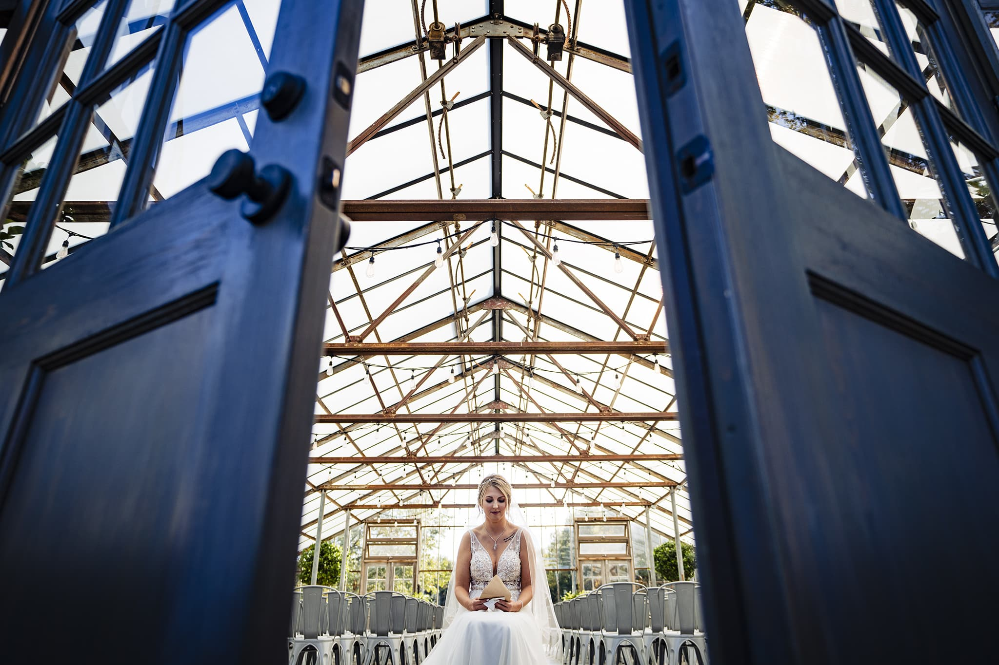Bride reads note from groom in modern greenhouse wedding