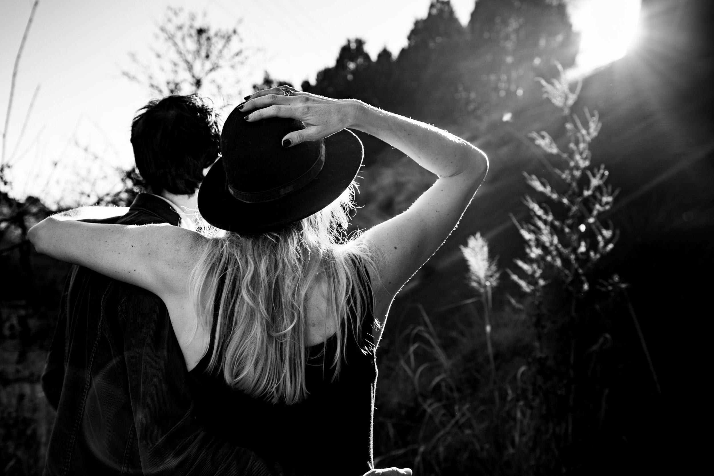 Woman holds hat as she and man look at the sunset in Austin by Austin Wedding Photographer Studio 22 Photography