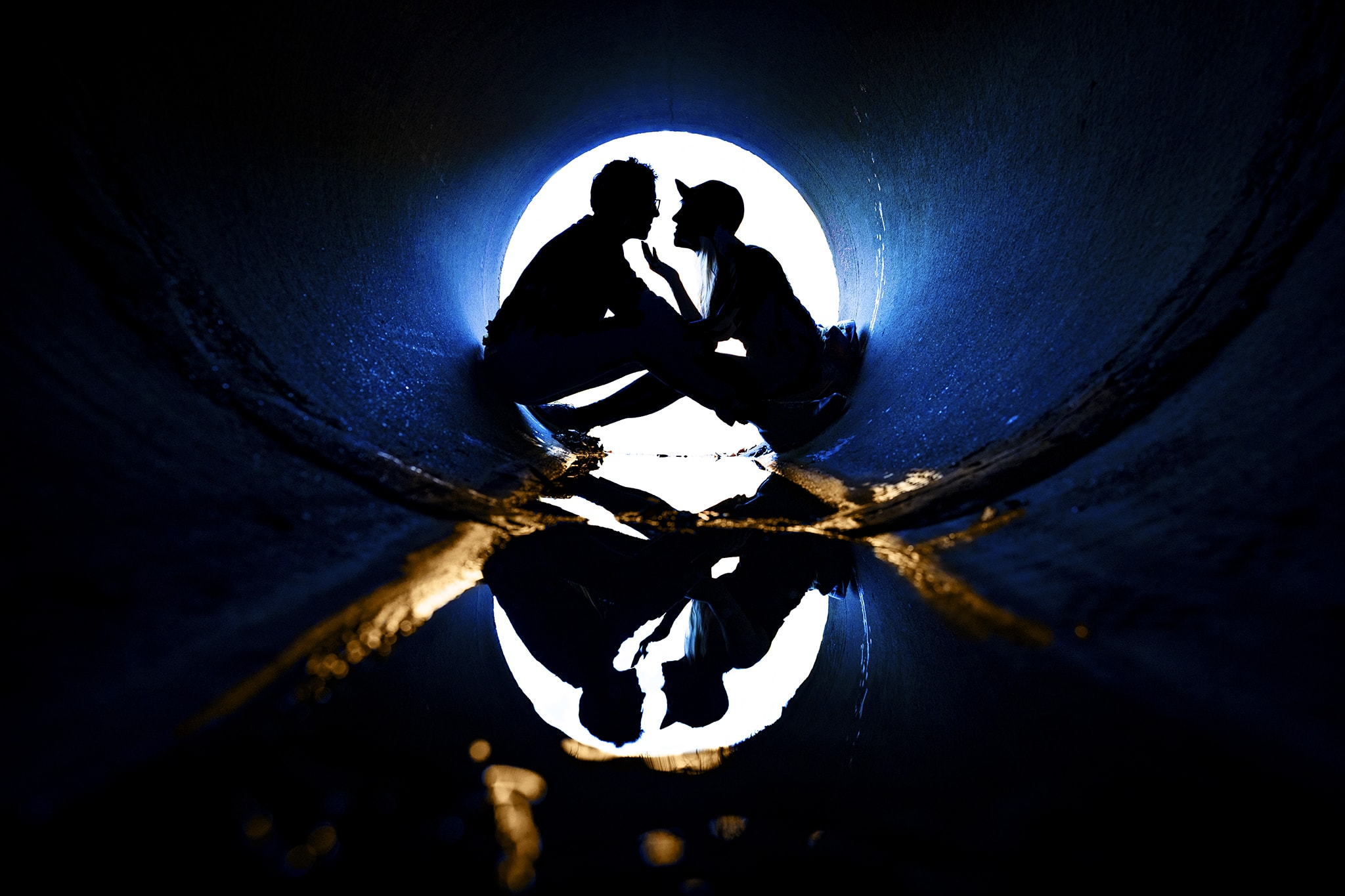 Couple silhouetted and reflected in water