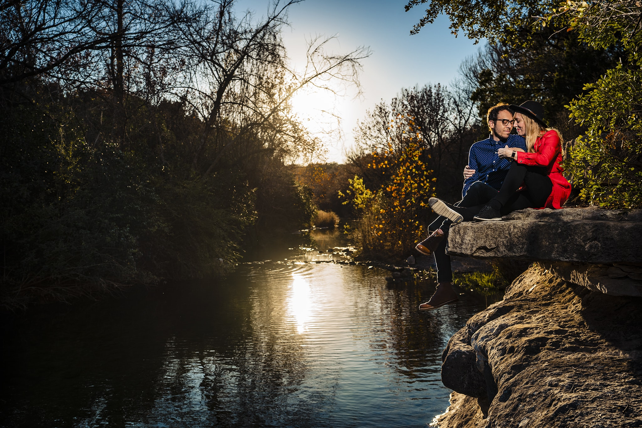 Man and woman snuggle together by a river in Austin by Austin Wedding Photographer Studio 22 Photography