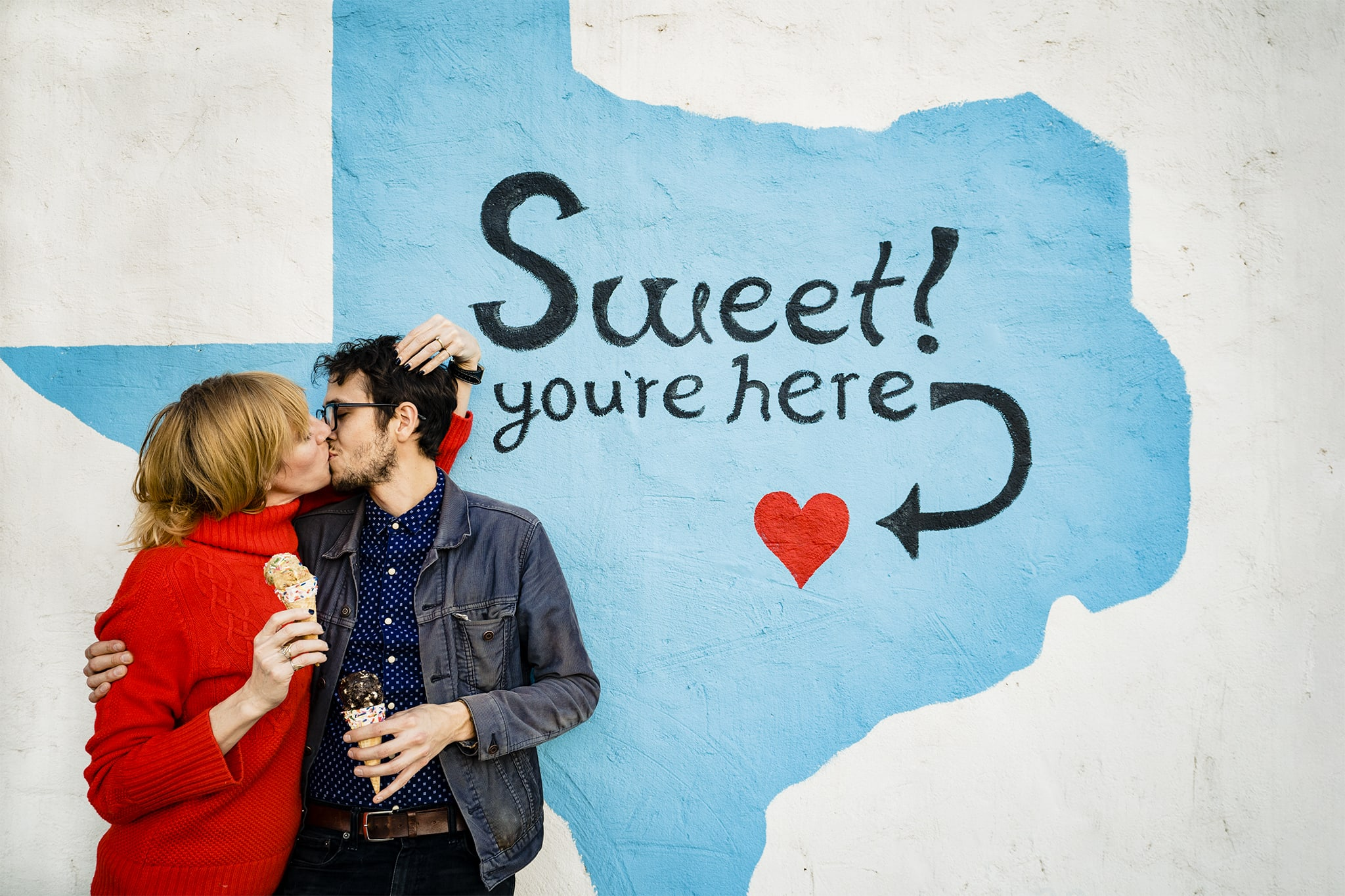 Man and woman kiss in front of Austin mural with ice cream at Kelli's Baking Co in Austin by Austin Wedding Photographer Studio 22 Photography