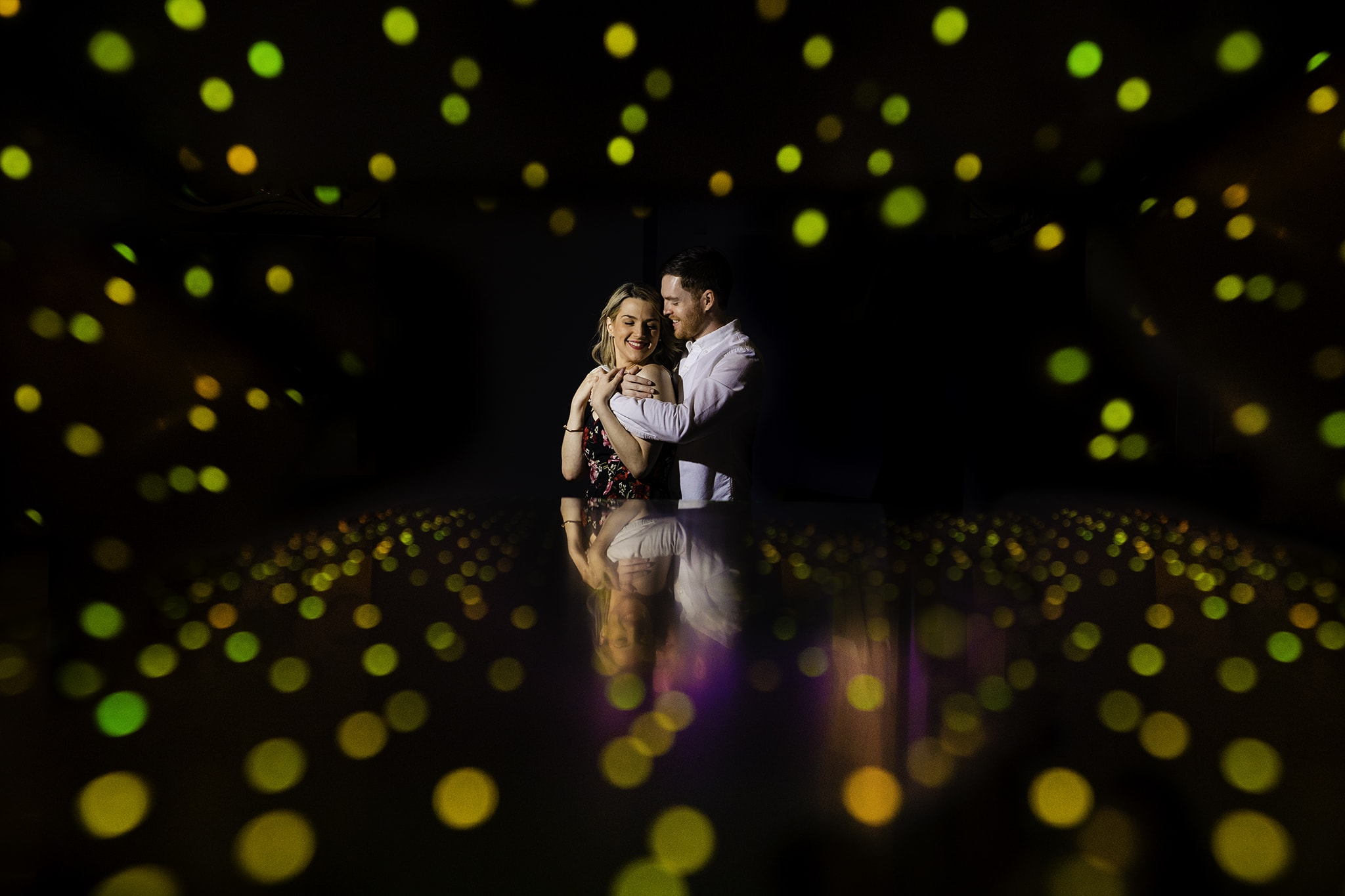 Man wraps arms around woman with lights all around them at Aloft Hotel in downtown Orlando by Orlando Wedding Photographer Studio 22 Photography