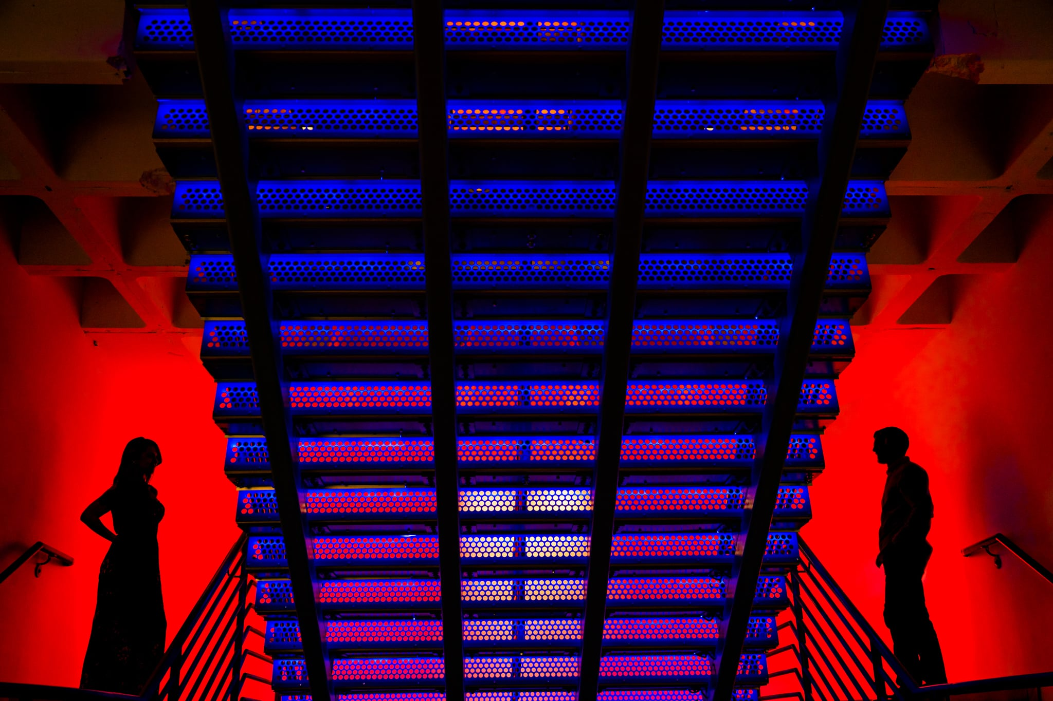Red silhouettes of a man and woman on either side of of the photo, looking in at one another, with a blue staircase in the middle at Aloft Hotel in Orlando by Dayton Wedding Photographer Studio 22 Photography