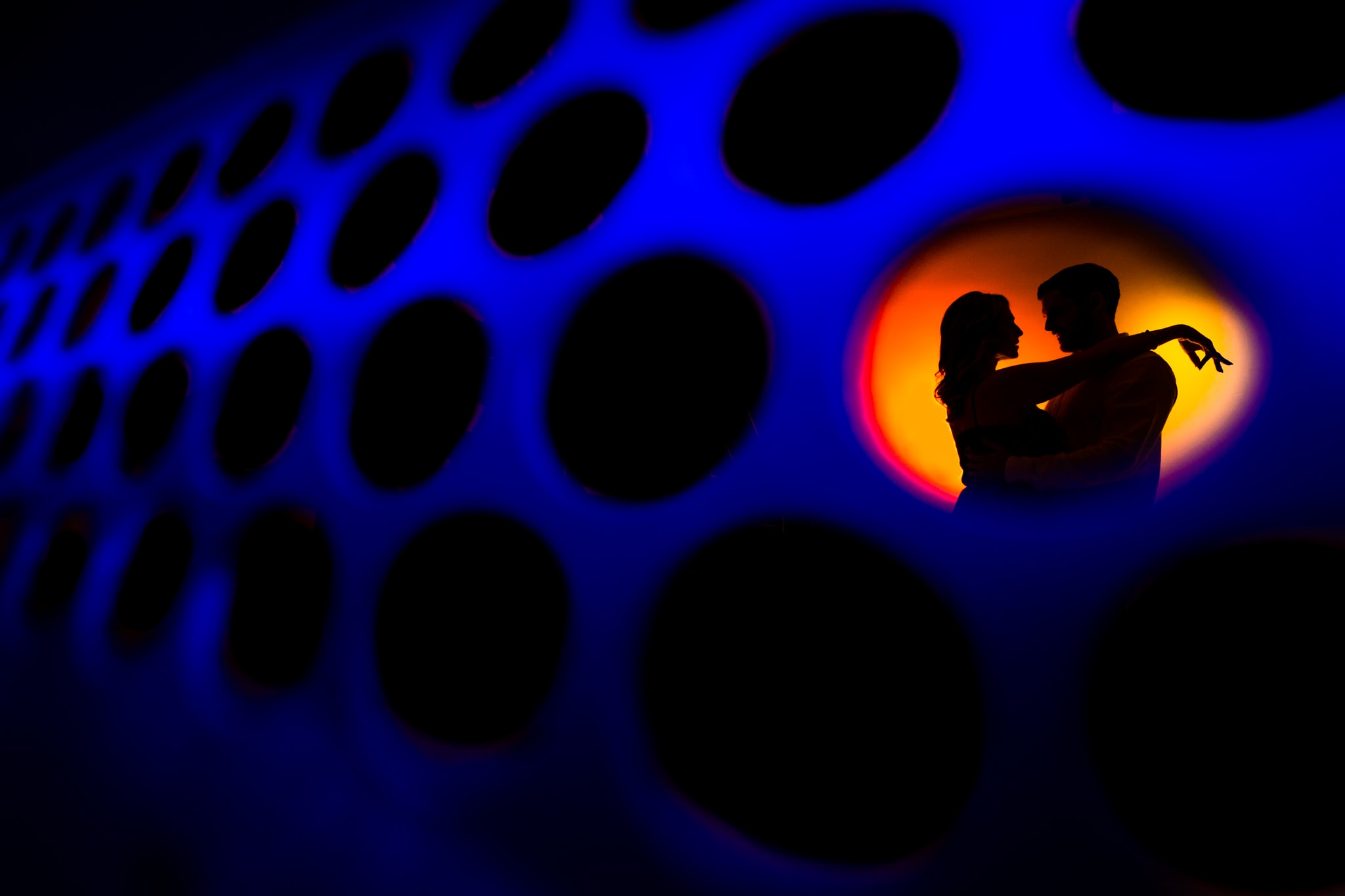 Silhouetted woman puts arms over man's shoulder in an orange circle with blue tones around them at Aloft Hotel in Orlando by Orlando Wedding Photographer Studio 22 Photography