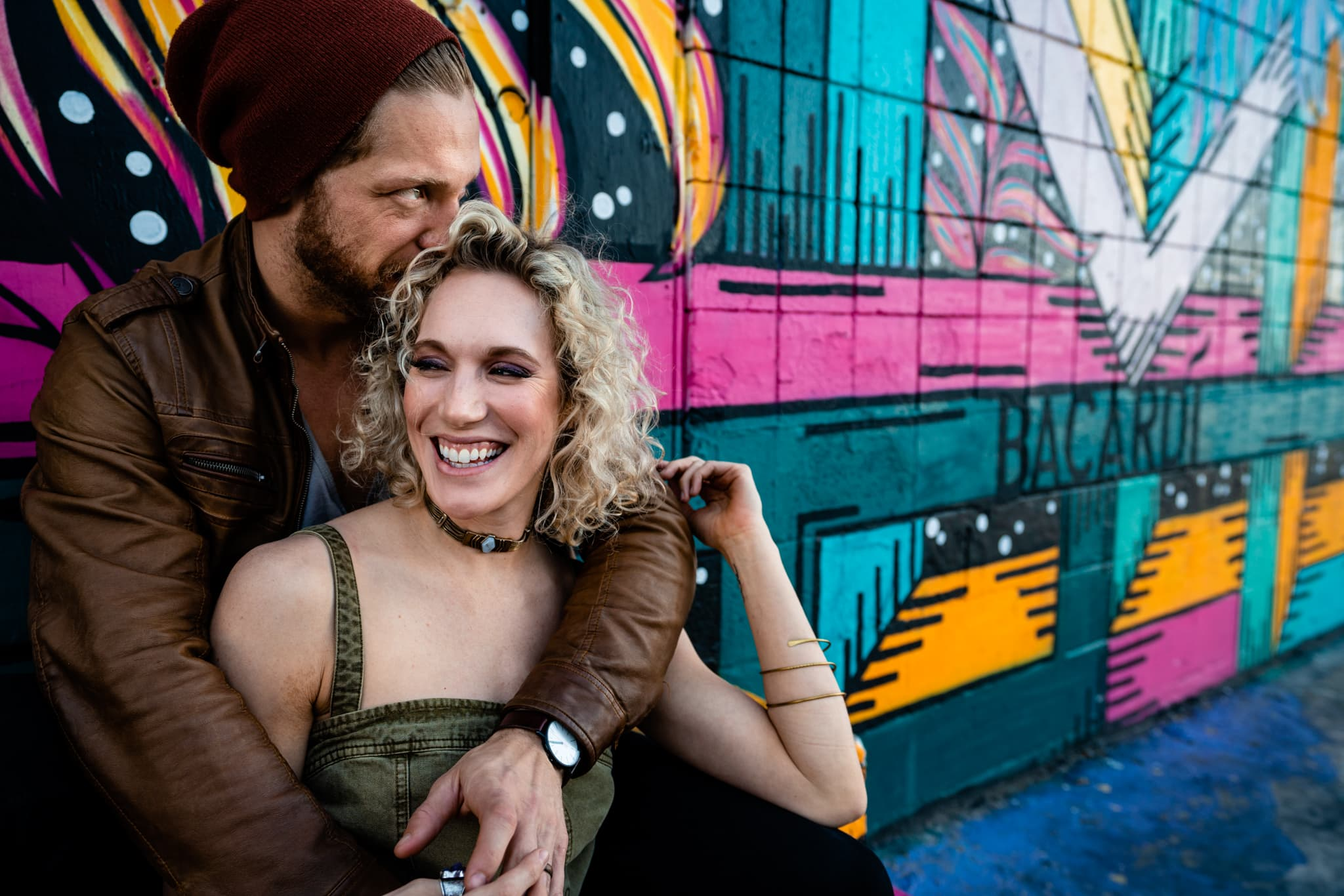 Man wraps arms around woman as they sit against graffiti on Fremont Street in Las Vegas by Las Vegas Wedding Photographer Studio 22 Photography