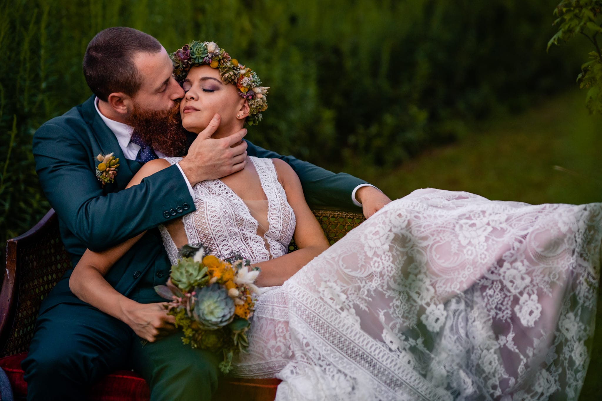 Groom kisses bride on a vintage couch in the woods after intimate elopement in Cincinnati, Ohio by Dayton Wedding Photographer Studio 22 Photography