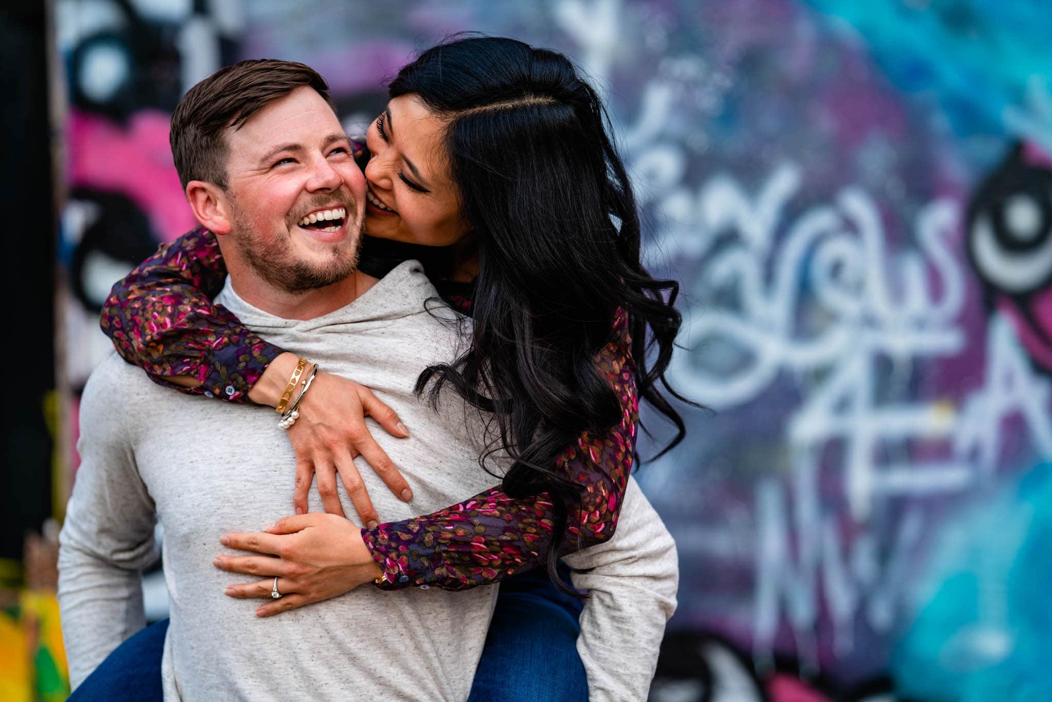Woman hops on man's back and gives him a kiss as the man smiles. They are in front of a graffiti wall in Downtown Dayton, Ohio, having their engagement session photographed.