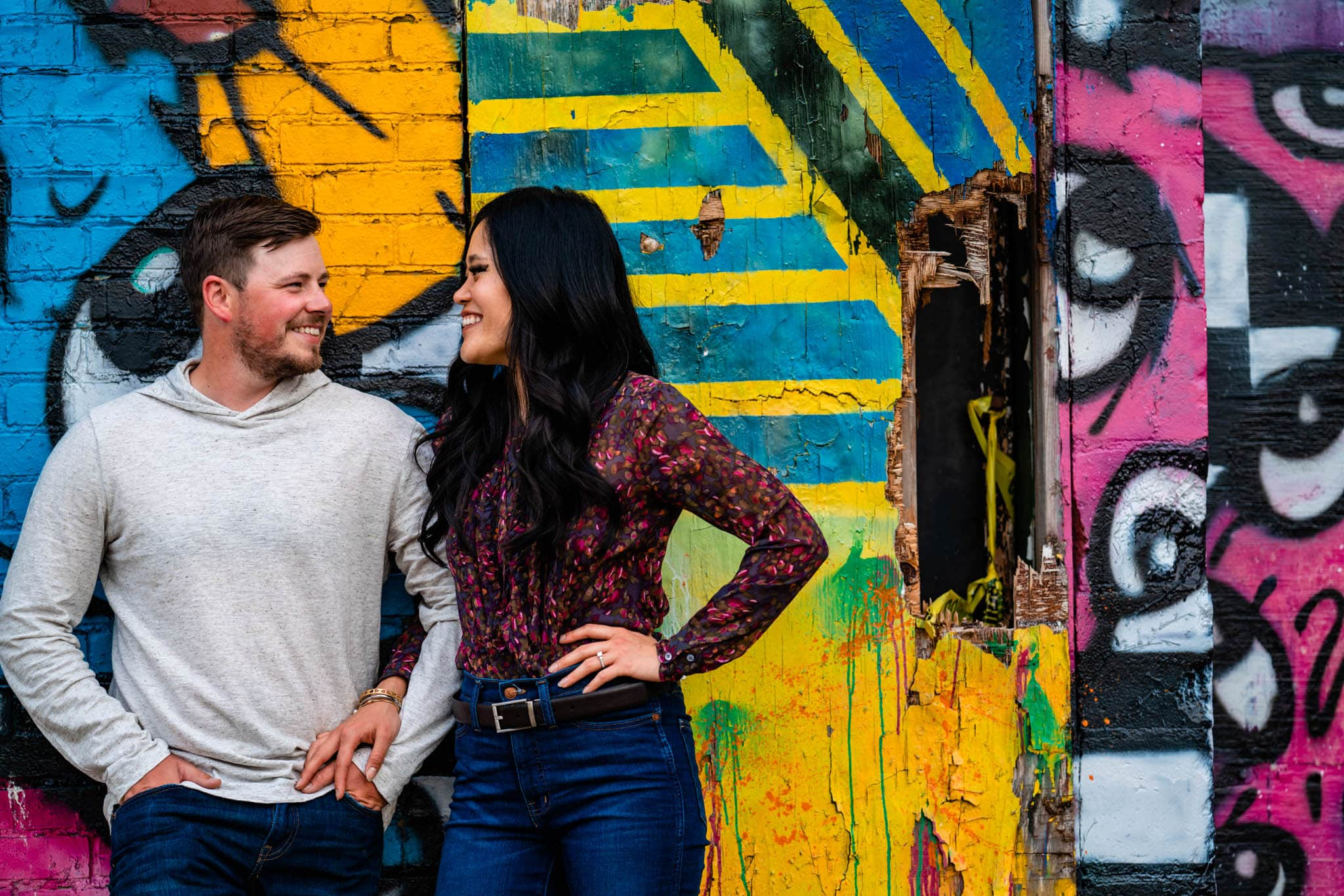 Man and woman stand together in front of colorful graffiti wall in downtown Dayton for their summer engagement photos.