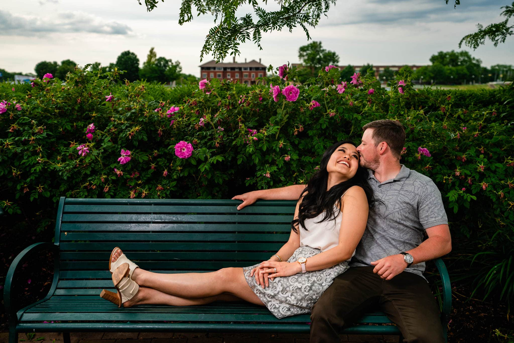 Man and woman sit together at Riverscape Metro Park in Dayton, Ohio while having their engagement photos taken.