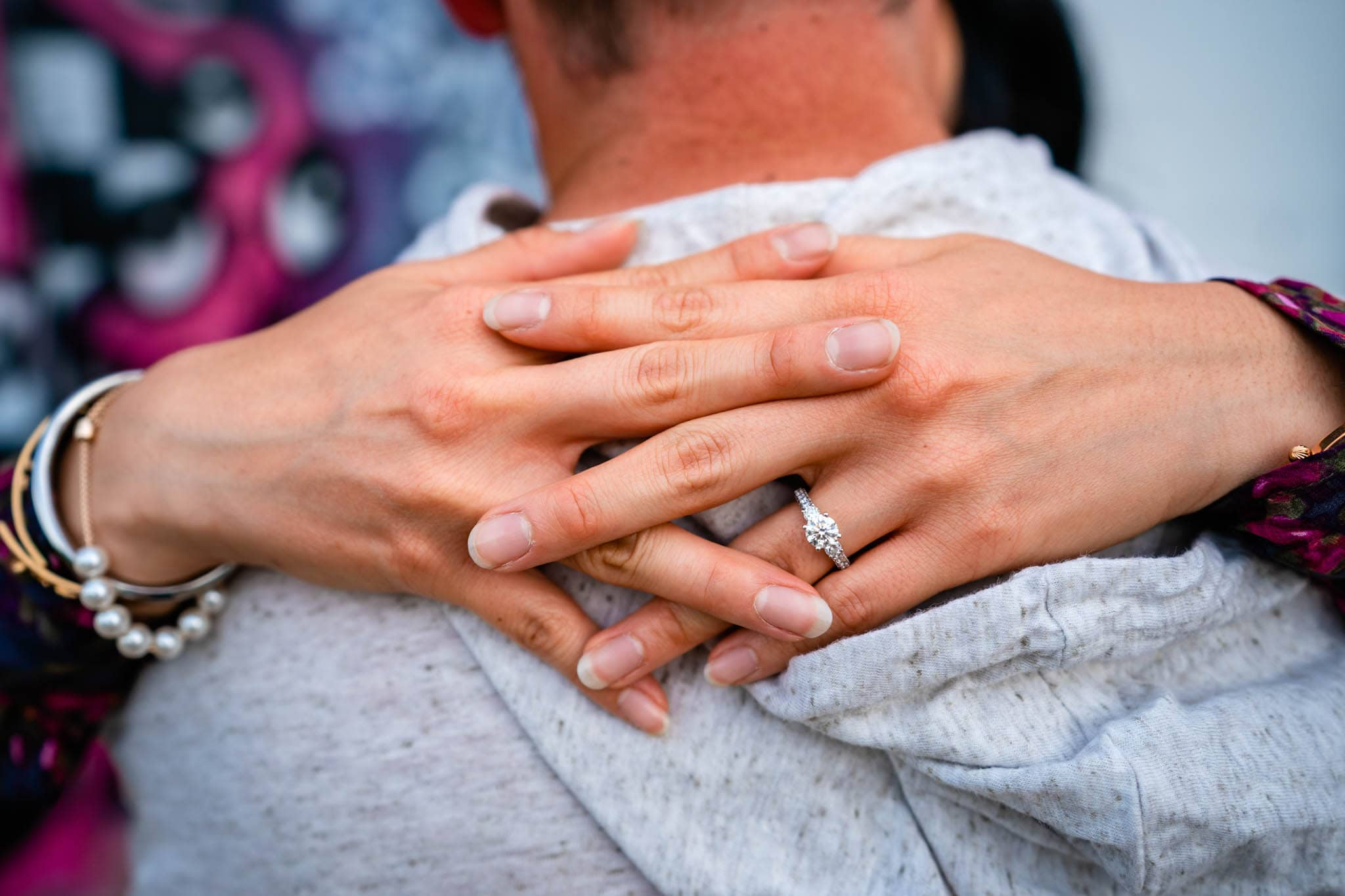 Woman wraps her arms around her fiance and shows her engagement ring in downtown Dayton.