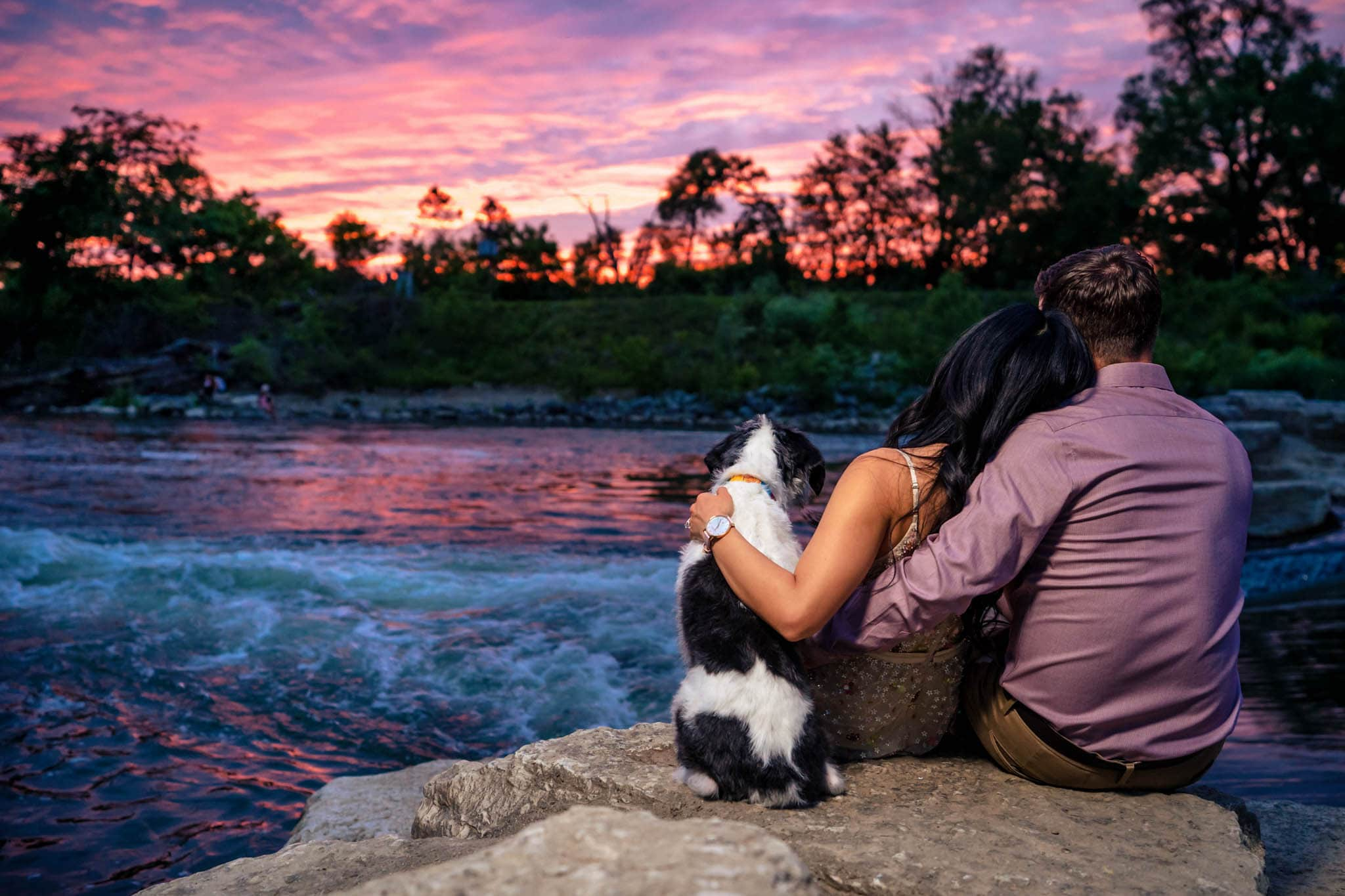 Man, woman, and their dog enjoy a beautiful pink sunset at Eastwood Metro Park in downtown Dayton during their summer engagement session with Megan Allen of Studio 22 Photography